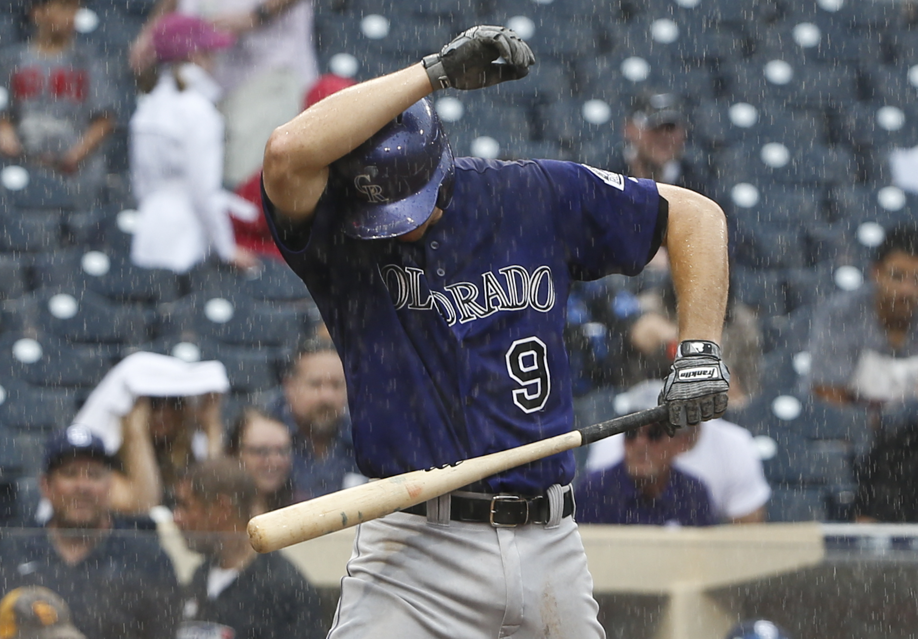 Colorado Rockies' DJ LeMahieu covers his head as he tries to bat in a rain storm in the fifth inning of a baseball game against the San Diego Padres Sunday, July 19, 2015, in San Diego.   (AP Photo/Lenny Ignelzi)