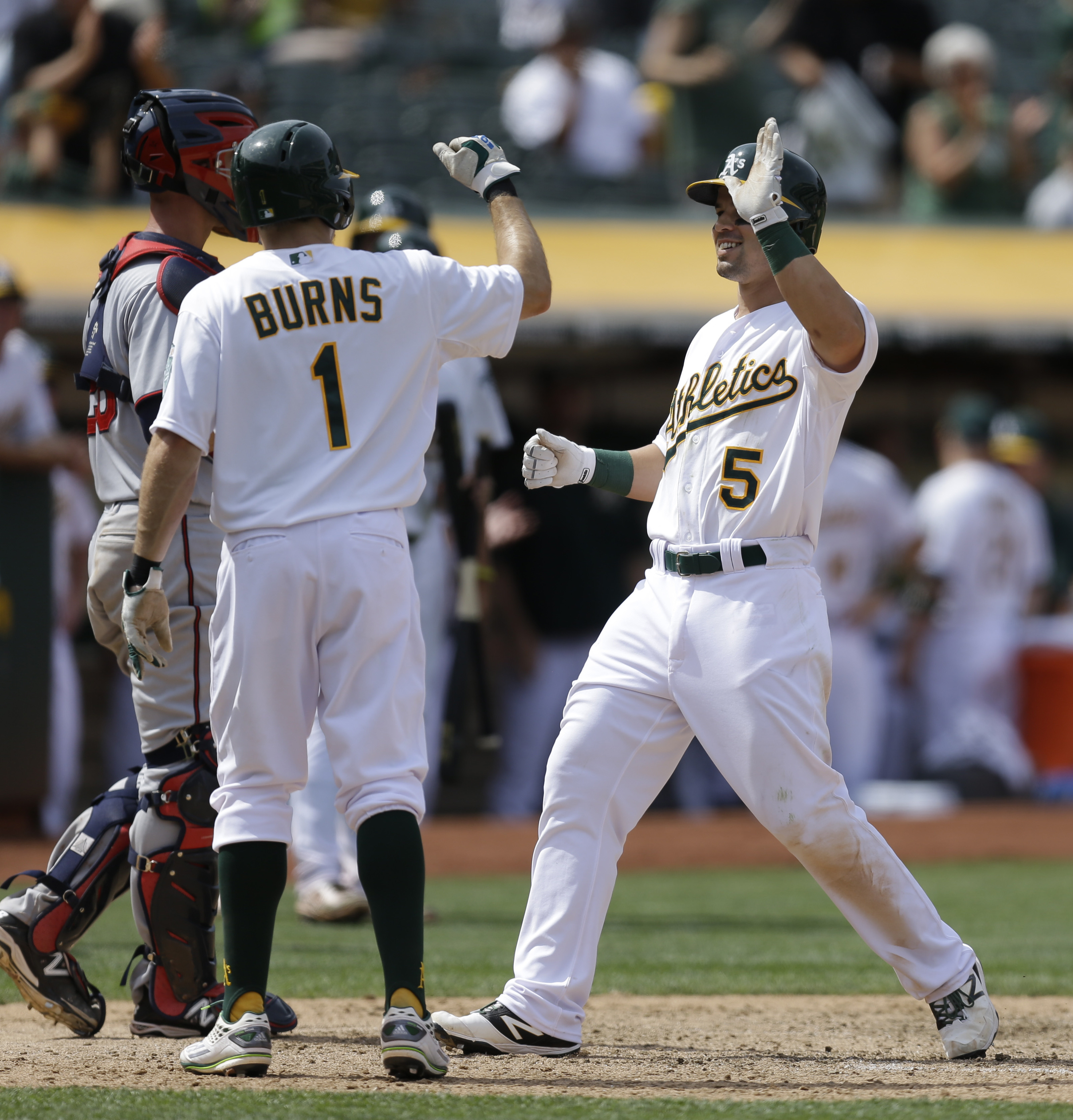 Oakland Athletics' Jake Smolinski, right, is congratulated by Billy Burns (1) after hitting a three-run home run off Minnesota Twins' Trevor May in the eighth inning of a baseball game Sunday, July 19, 2015, in Oakland, Calif. (AP Photo/Ben Margot)
