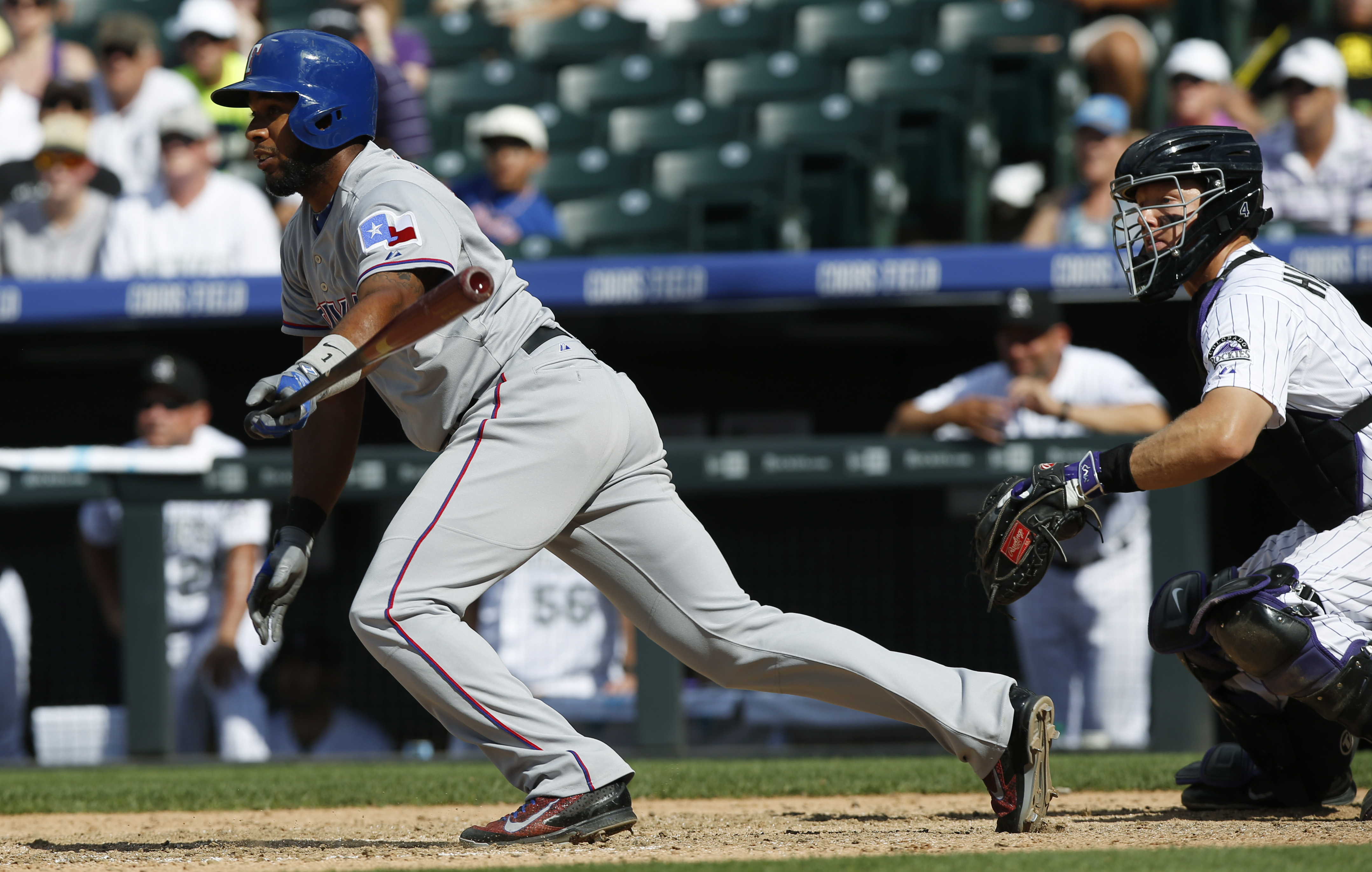 Texas Rangers' Elvis Andrus, left, follows the flight of his single to drive in two runs off Colorado Rockies relief pitcher John Axford in the ninth inning of an inter league baseball game Wednesday, July 22, 2015, in Denver. Colorado catcher Nick Hundle