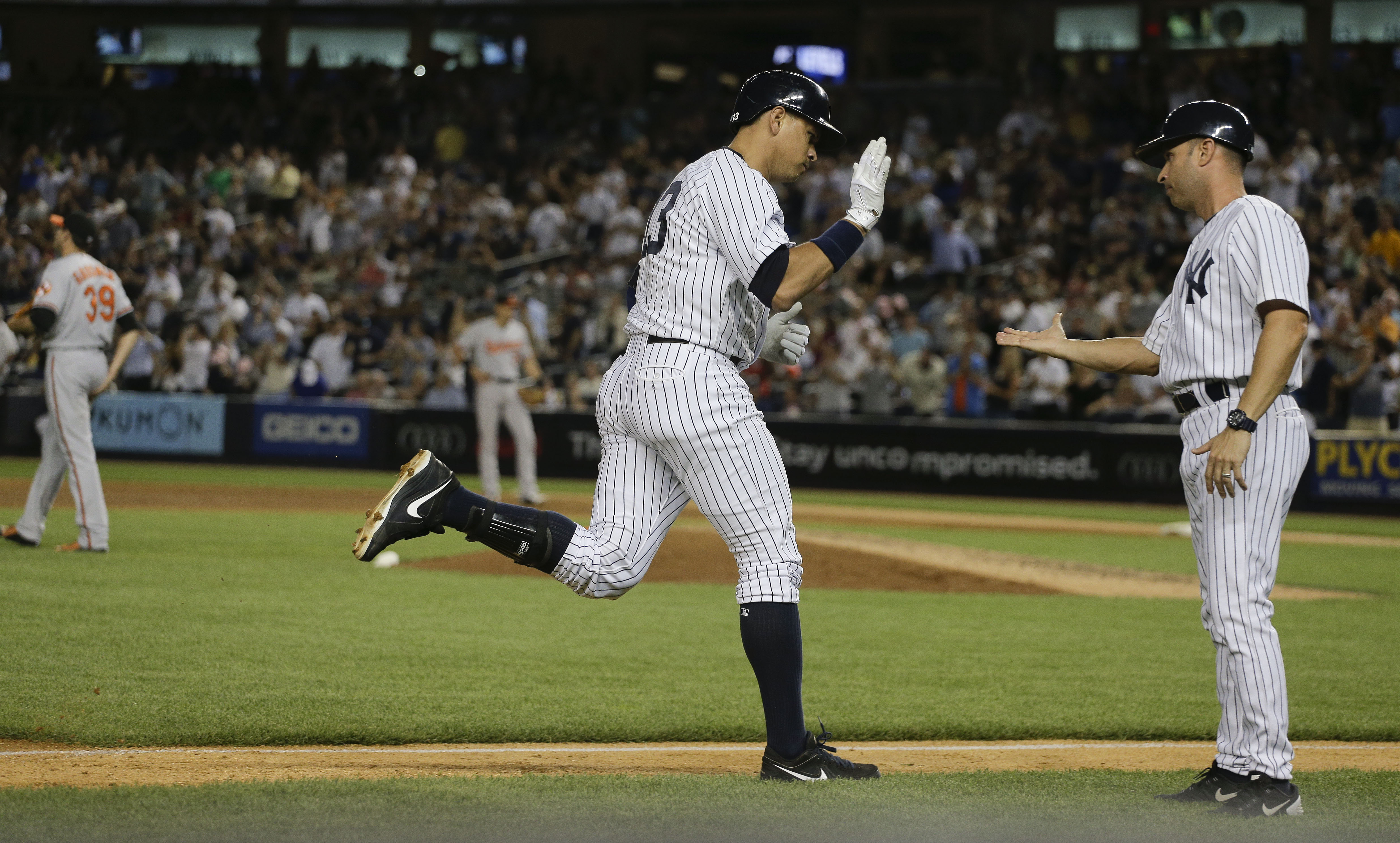 New York Yankees designated hitter Alex Rodriguez is greeted by third base coach Joe Espada as he rounds the bases after hitting a solo home run against the Baltimore Orioles during the fifth inning of a baseball game, Wednesday, July 22, 2015, in New Yor
