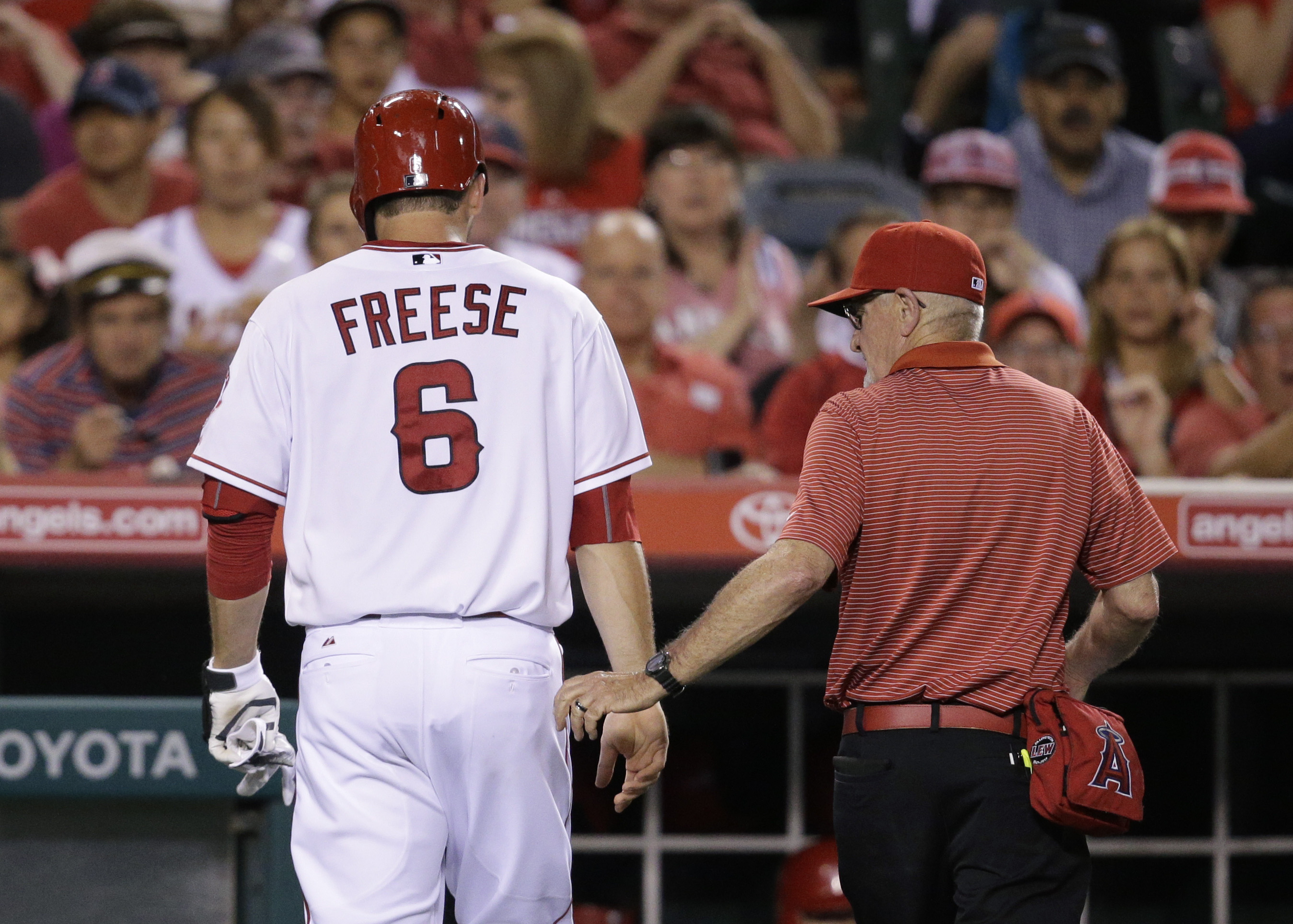 Los Angeles Angels' David Freese, left, walks off the field with a trainer after he was hit by a pitch during the fourth inning of a baseball game against the Minnesota Twins, Wednesday, July 22, 2015, in Anaheim, Calif. (AP Photo/Jae C. Hong)