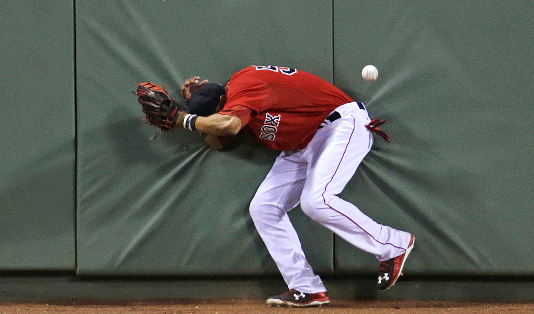 Boston Red Sox center fielder Mookie Betts hits the wall after losing track of the ball on a triple by Detroit Tigers' Ian Kinsler during the eighth inning of a baseball game at Fenway Park in Boston, Friday, July 24, 2015. (AP Photo/Charles Krupa)