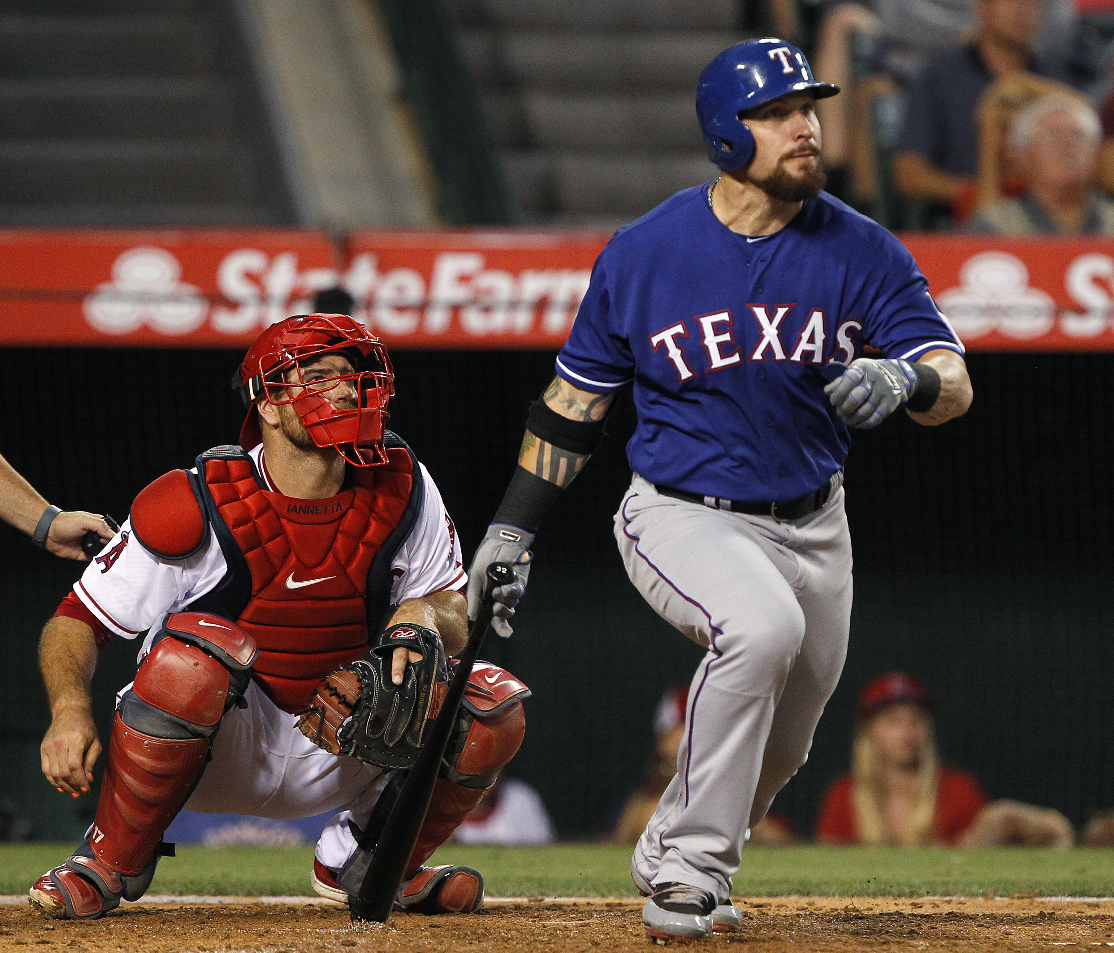 Texas Rangers' Josh Hamilton, right, watches his double in front of Los Angeles Angels catcher Chris Iannetta during the fifth inning of a baseball game in Anaheim, Calif., Friday, July 24, 2015. (AP Photo/Alex Gallardo)