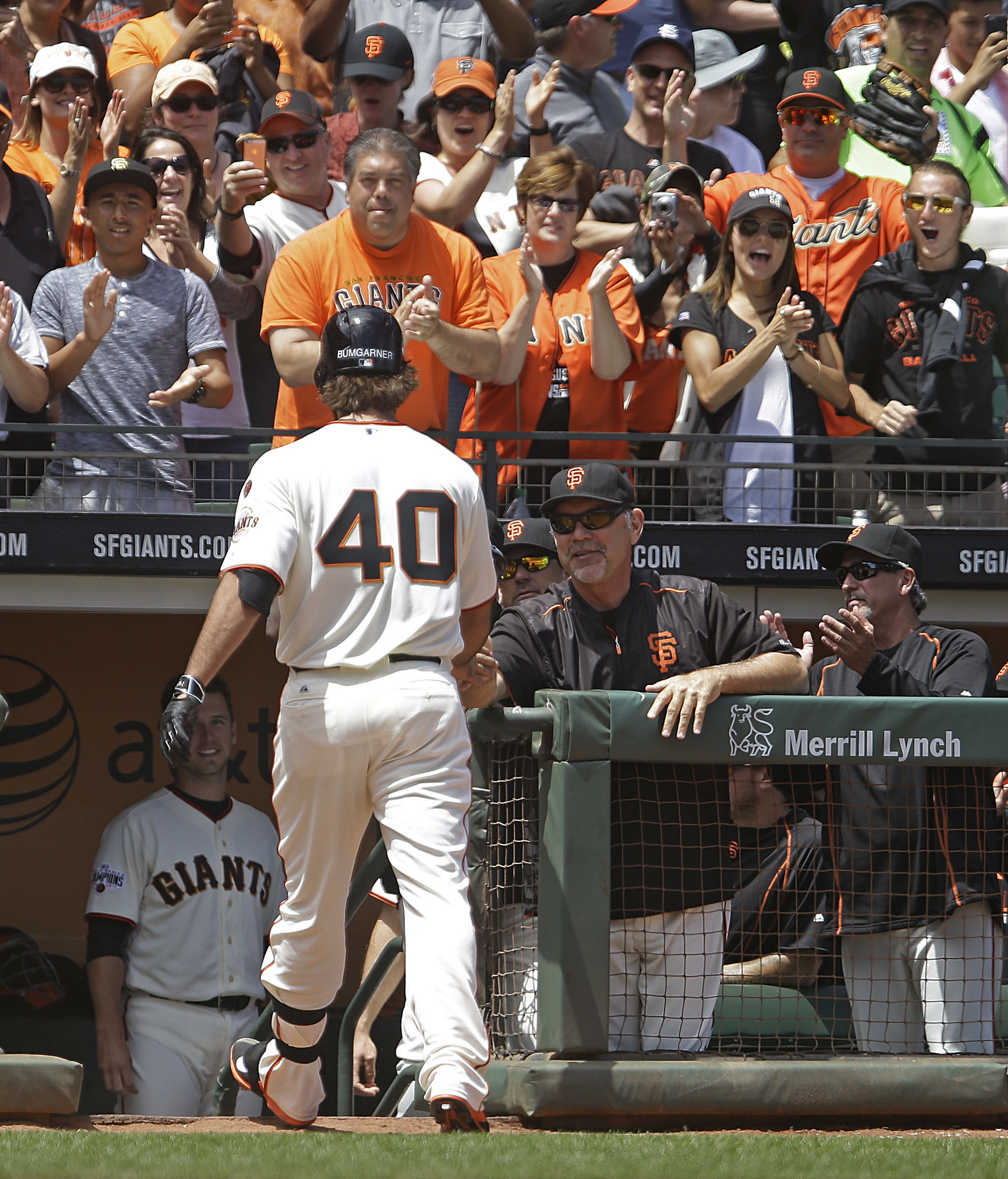 San Francisco Giants pitcher Madison Bumgarner (40) is congratulated by manageer Bruce Bochy after hitting a home run off Oakland Athletics' Chris Bassitt in the third inning of a baseball game Saturday, July 25, 2015, in San Francisco. (AP Photo/Ben Marg