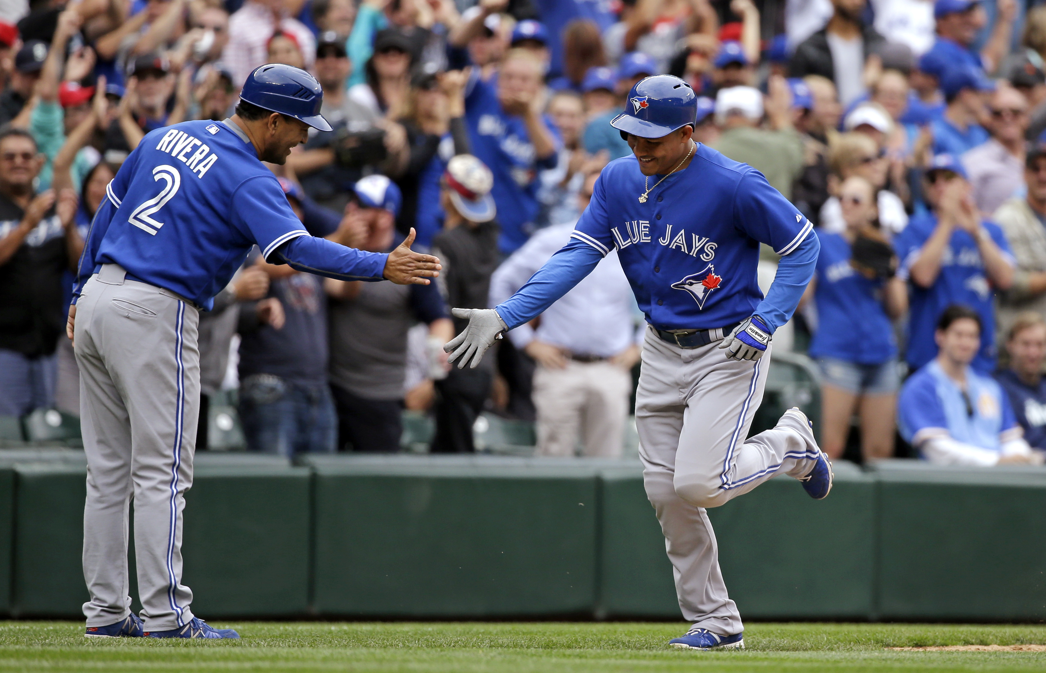 Toronto Blue Jays' Ezequiel Carrera, right, is congratulated by third base coach Luis Rivera on Carrera's two-run home run against the Seattle Mariners in the eighth inning of a baseball game Saturday, July 25, 2015, in Seattle. (AP Photo/Elaine Thompson)