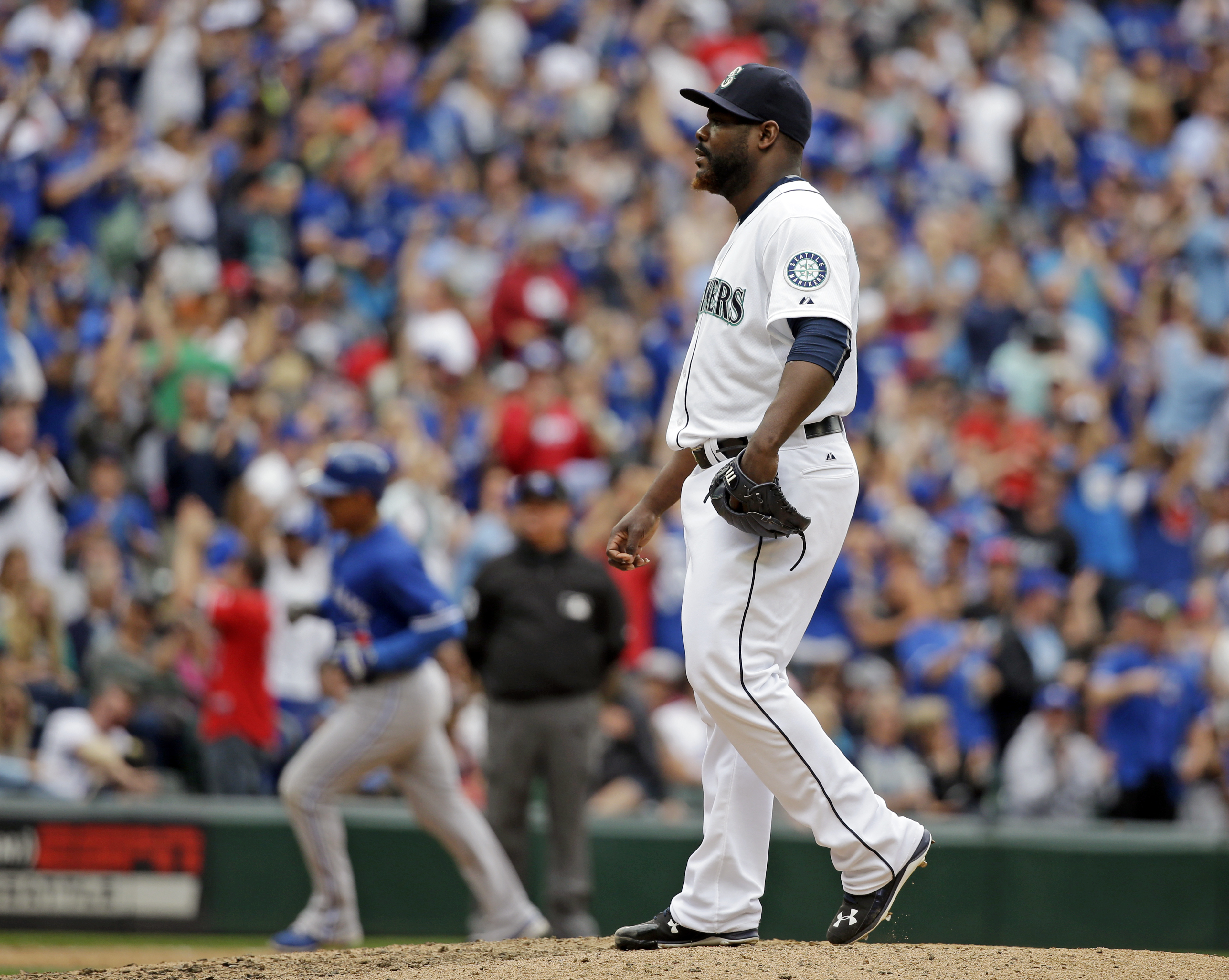 Seattle Mariners relief pitcher Fernando Rodney, right, waits on the mound as Toronto Blue Jays' Ezequiel Carrera rounds the bases after hitting a two-run home run in the eighth inning of a baseball game Saturday, July 25, 2015, in Seattle. (AP Photo/Elai