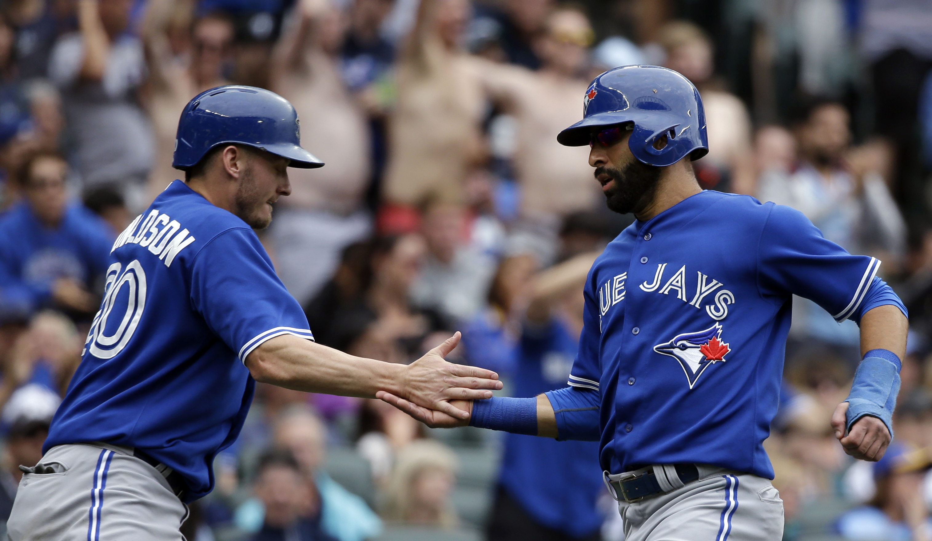 Toronto Blue Jays' Josh Donaldson, left, and Jose Bautista celebrate after they scored on a single by Chris Colabello against the Seattle Mariners in the ninth inning of a baseball game Saturday, July 25, 2015, in Seattle. (AP Photo/Elaine Thompson)