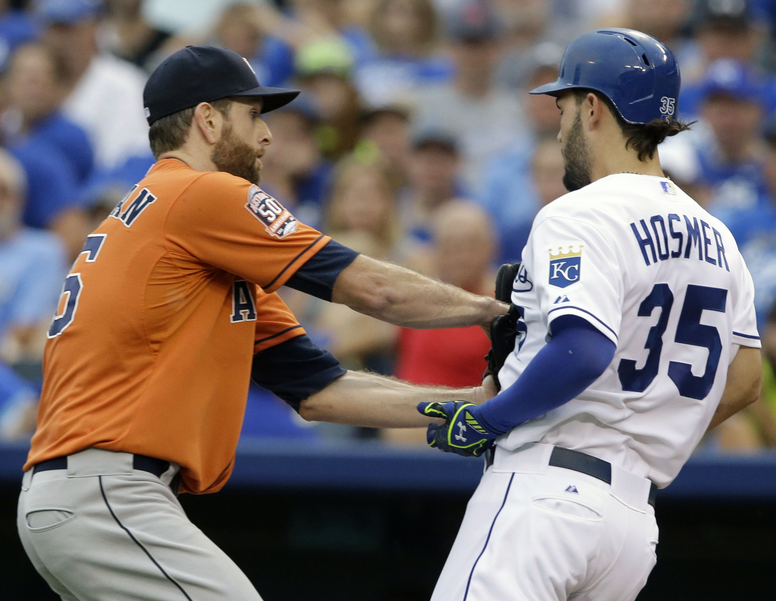 Houston Astros starting pitcher Scott Feldman, left, tags out Kansas City Royals' Eric Hosmer (35) during the fifth inning of a baseball game at Kauffman Stadium in Kansas City, Mo., Saturday, July 25, 2015. (AP Photo/Orlin Wagner)