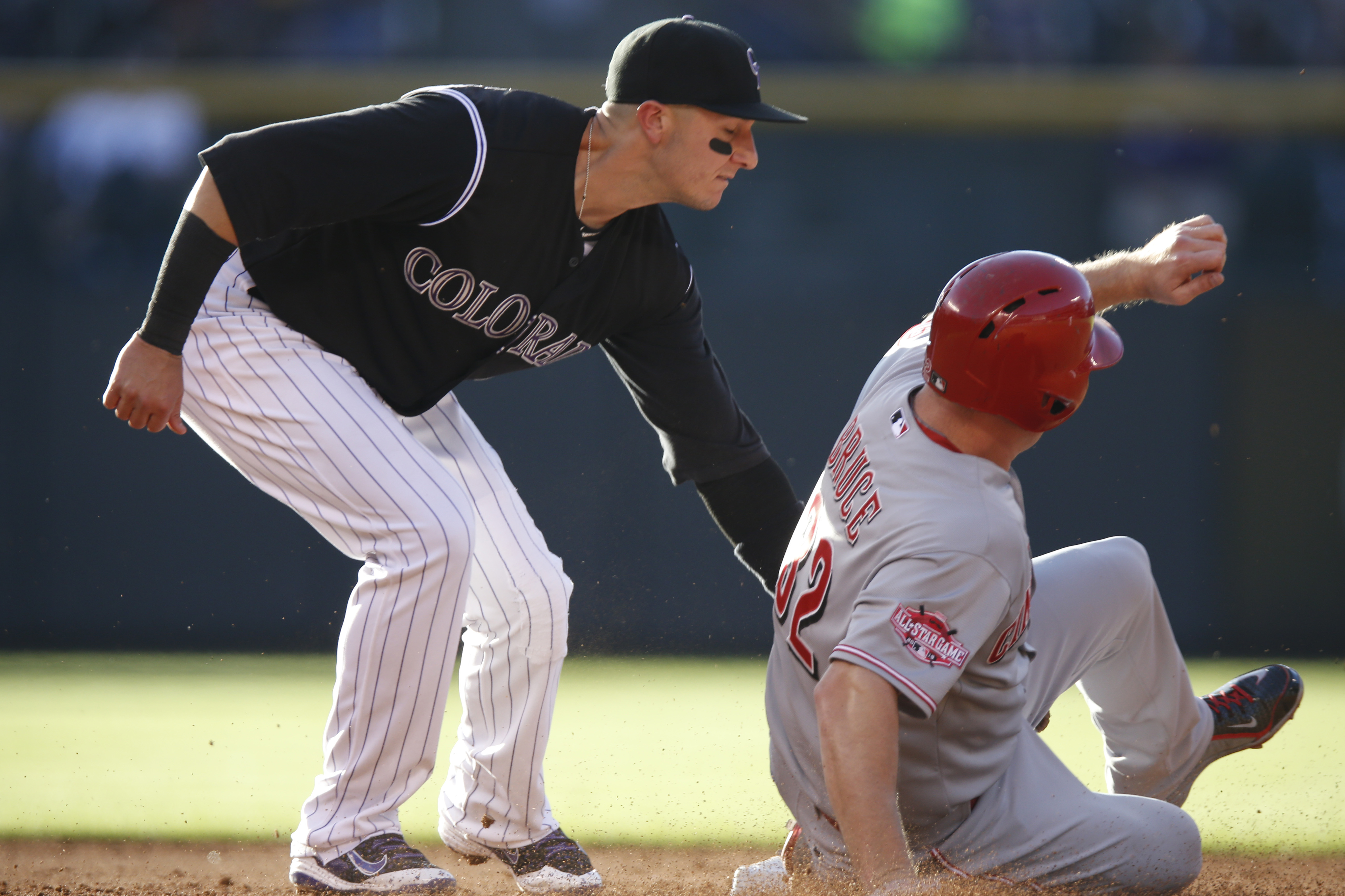 Colorado Rockies shortstop Troy Tulowitzki , left, tags out Cincinnati Reds' Jay Bruce as he tries to steal second base in the third inning of a baseball game Saturday, July 25, 2015, in Denver. (AP Photo/David Zalubowski)