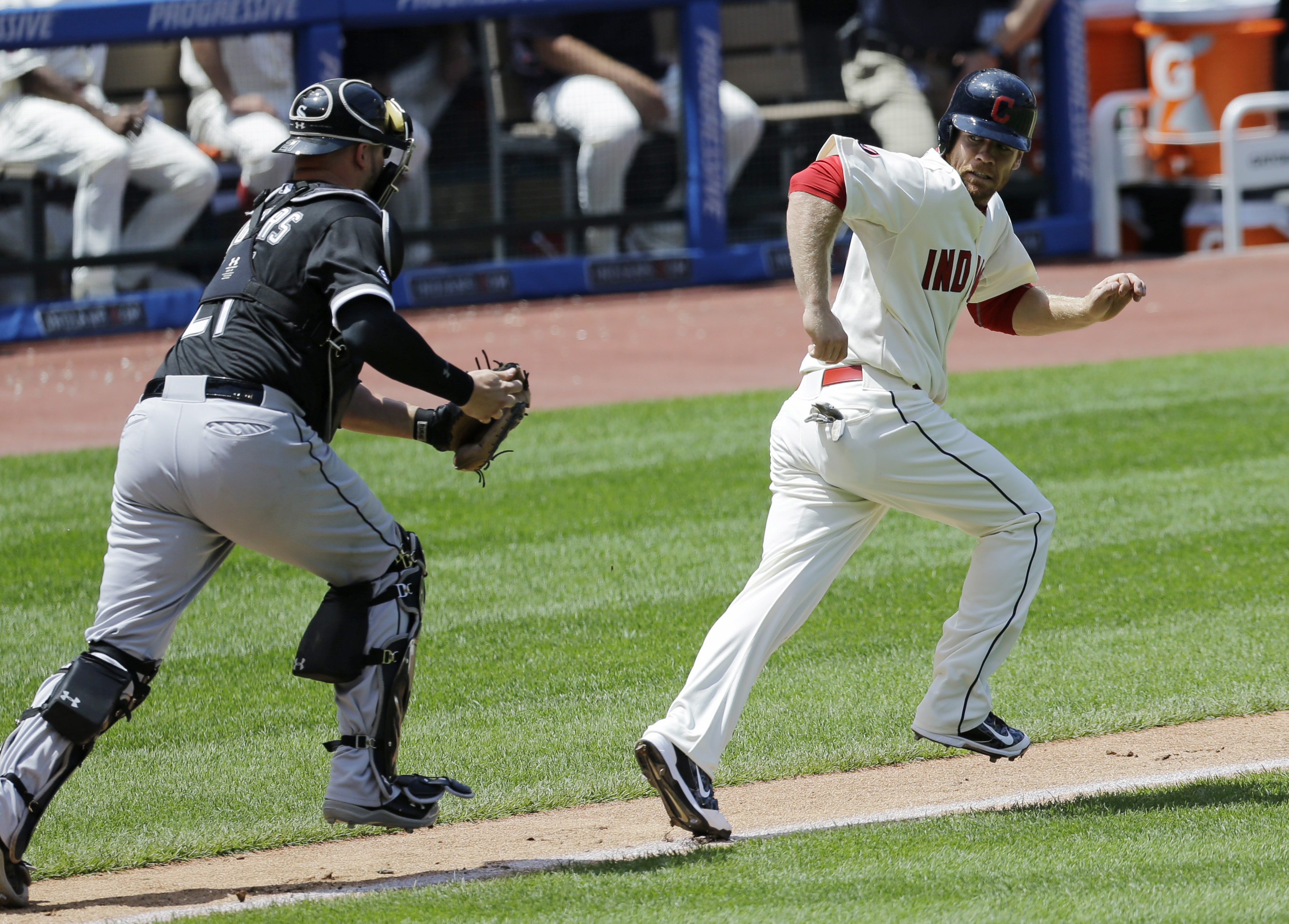 Cleveland Indians' Brandon Moss, right, looks back as Chicago White Sox catcher Tyler Flowers chases him in the third inning of a baseball game, Sunday, July 26, 2015, in Cleveland. Moss was out on the play. (AP Photo/Tony Dejak)