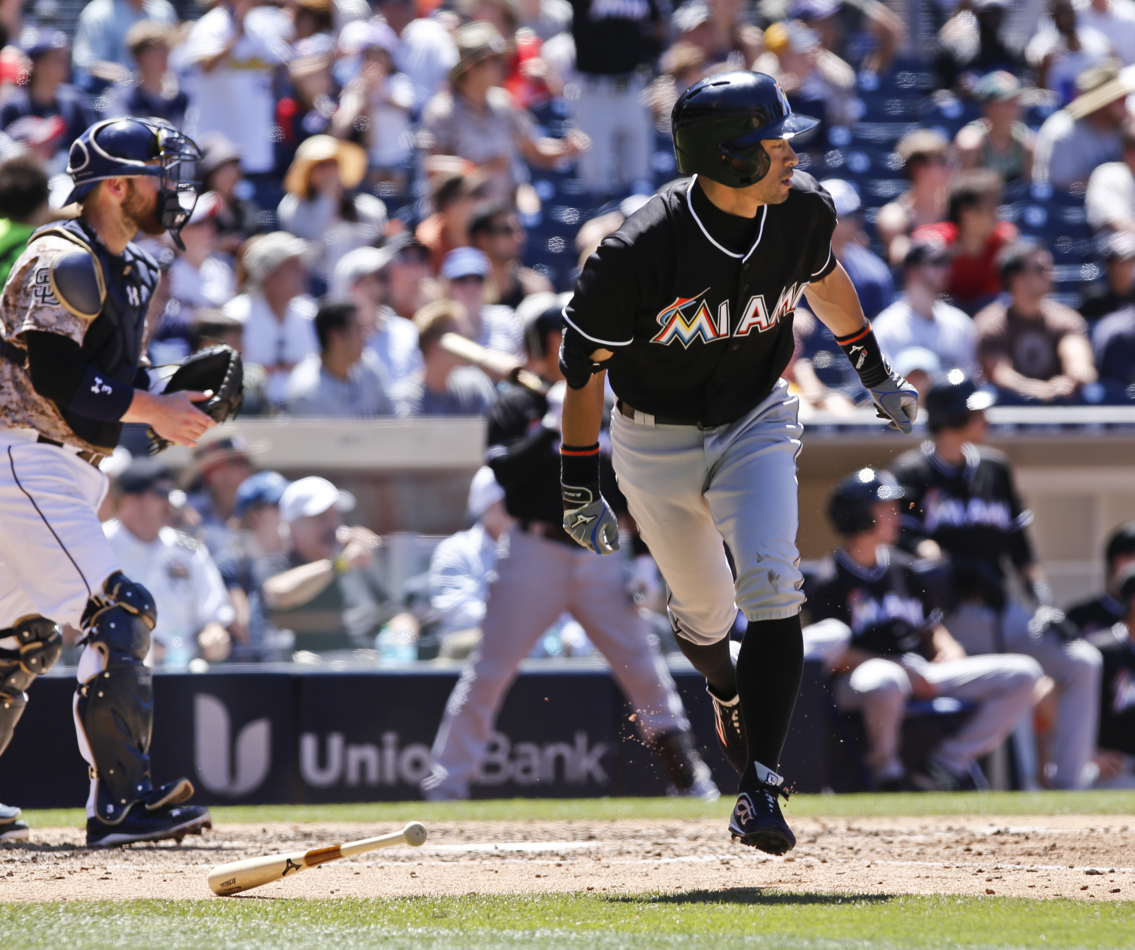 Miami Marlins' Ichiro Susuki watches his sacrifice fly to left field that scored J.T. Realmuto from third base against the San Diego Padres during the fifth inning in a baseball game Sunday, July 26, 2015, in San Diego.  (AP Photo/Don Boomer)
