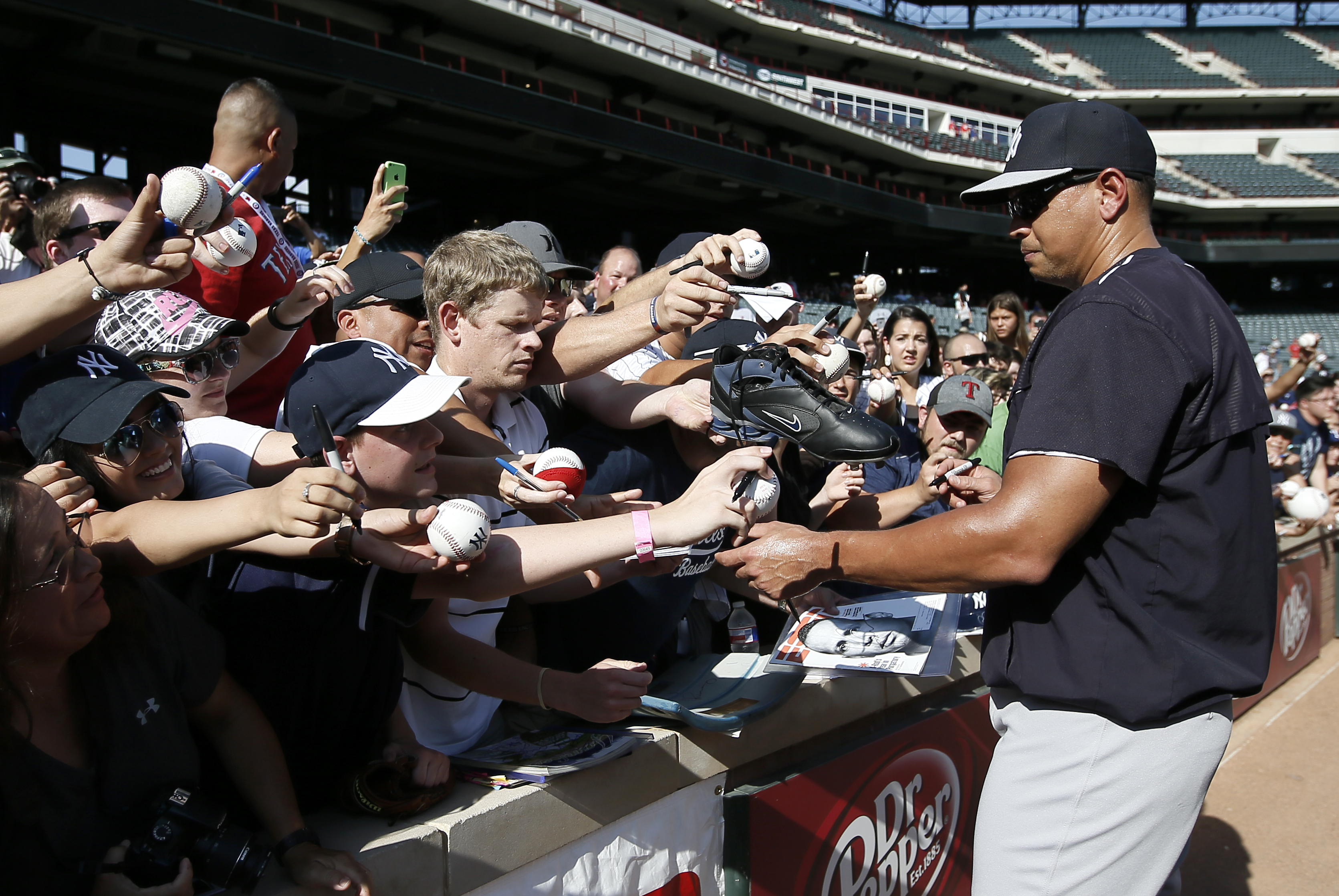 New York Yankees' Alex Rodriguez signs autographs for fans before a baseball game against the Texas Rangers, Monday,July 27, 2015, in Arlington, Texas. (AP Photo/Tony Gutierrez)
