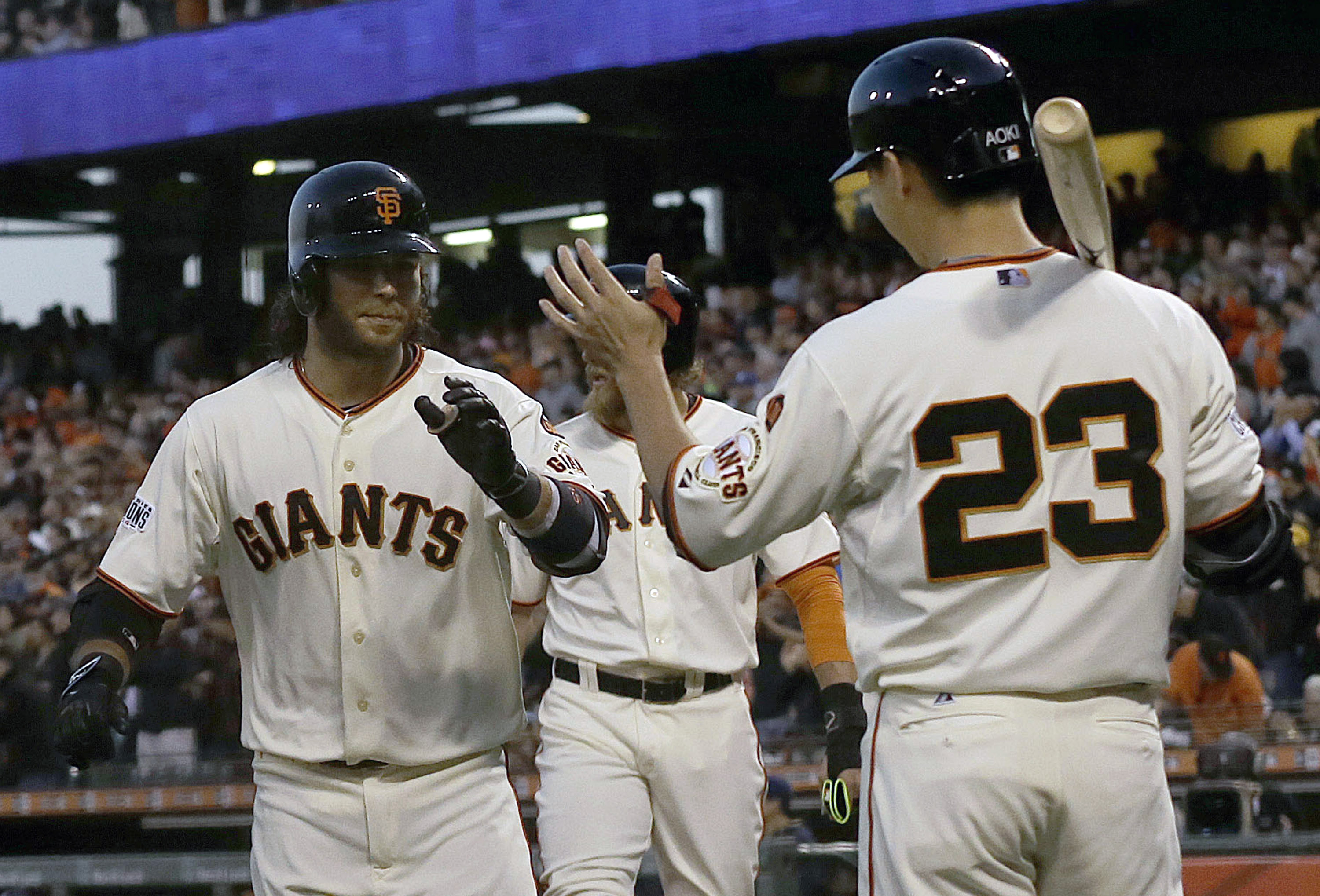 San Francisco Giants' Brandon Crawford, left, is congratulated by Nori Aoki (23) after hitting a two-run home run that scored Hunter Pence, rear, against the Milwaukee Brewers during the fourth inning of a baseball game in San Francisco, Monday, July 27,