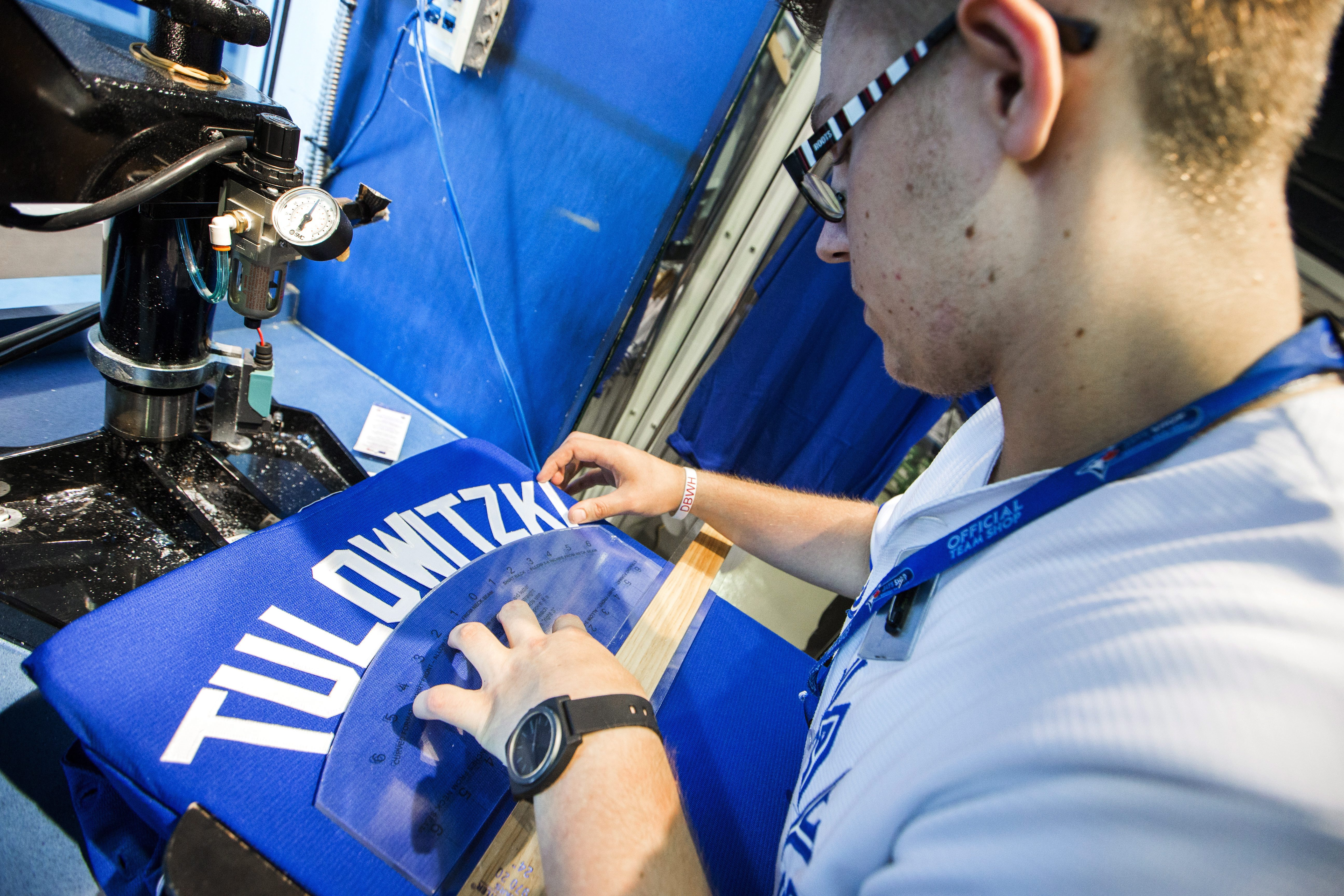 Toronto Blue Jays store employee Nico Canavo makes a Troy Tulowitzki jersey in Toronto, Tuesday July 28, 2015. The Colorado Rockies and Toronto Blue Jays have swapped star shortstops. The teams confirmed the blockbuster trade Tuesday, July 28, 2015, that