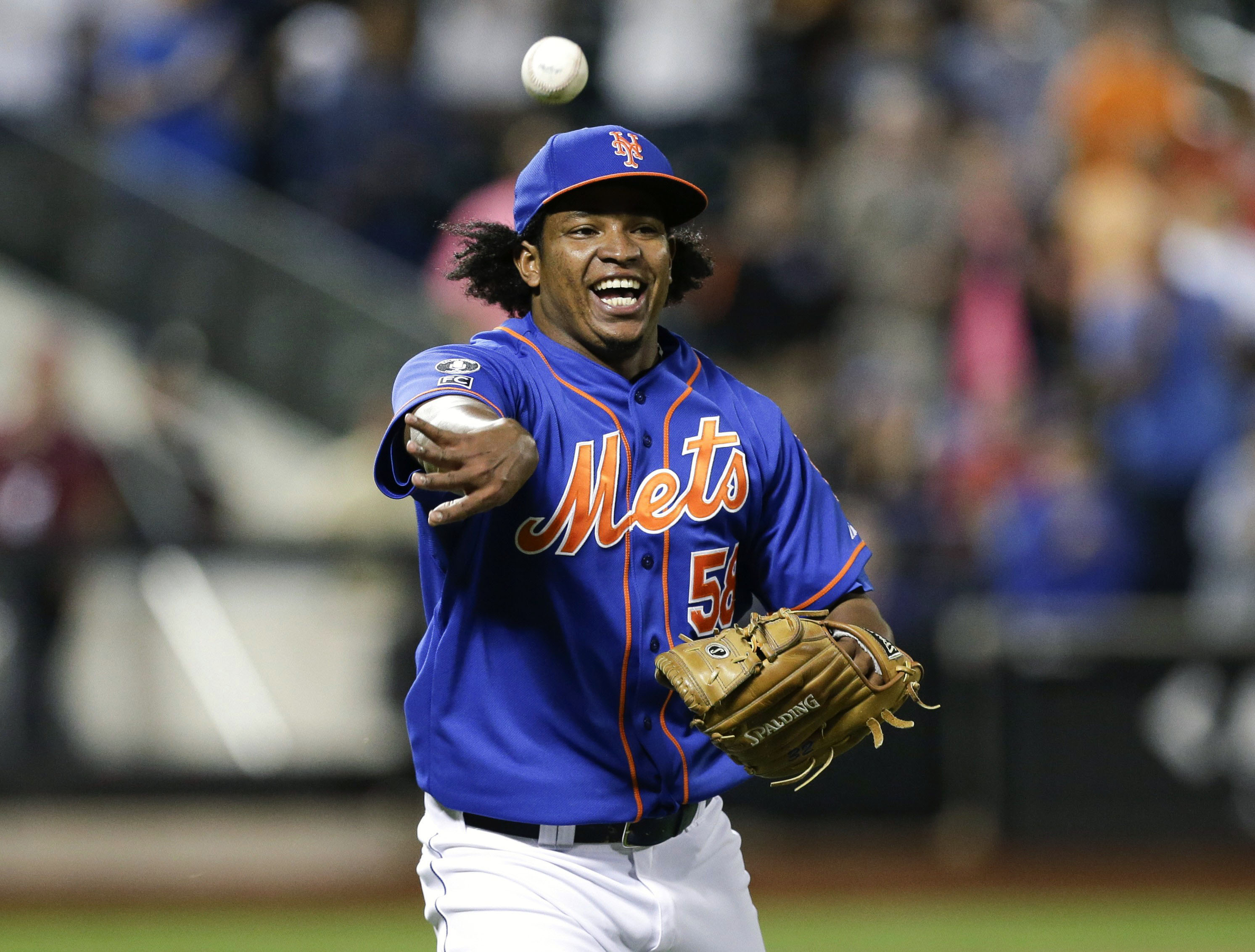 FILE - In this Wednesday, Sept. 10, 2014 file photo, New York Mets relief pitcher Jenrry Mejia tosses the ball to throw out Colorado Rockies' Josh Rutledge at first base to end a baseball game, in New York. Just back from an 80-game drug suspension, New Y