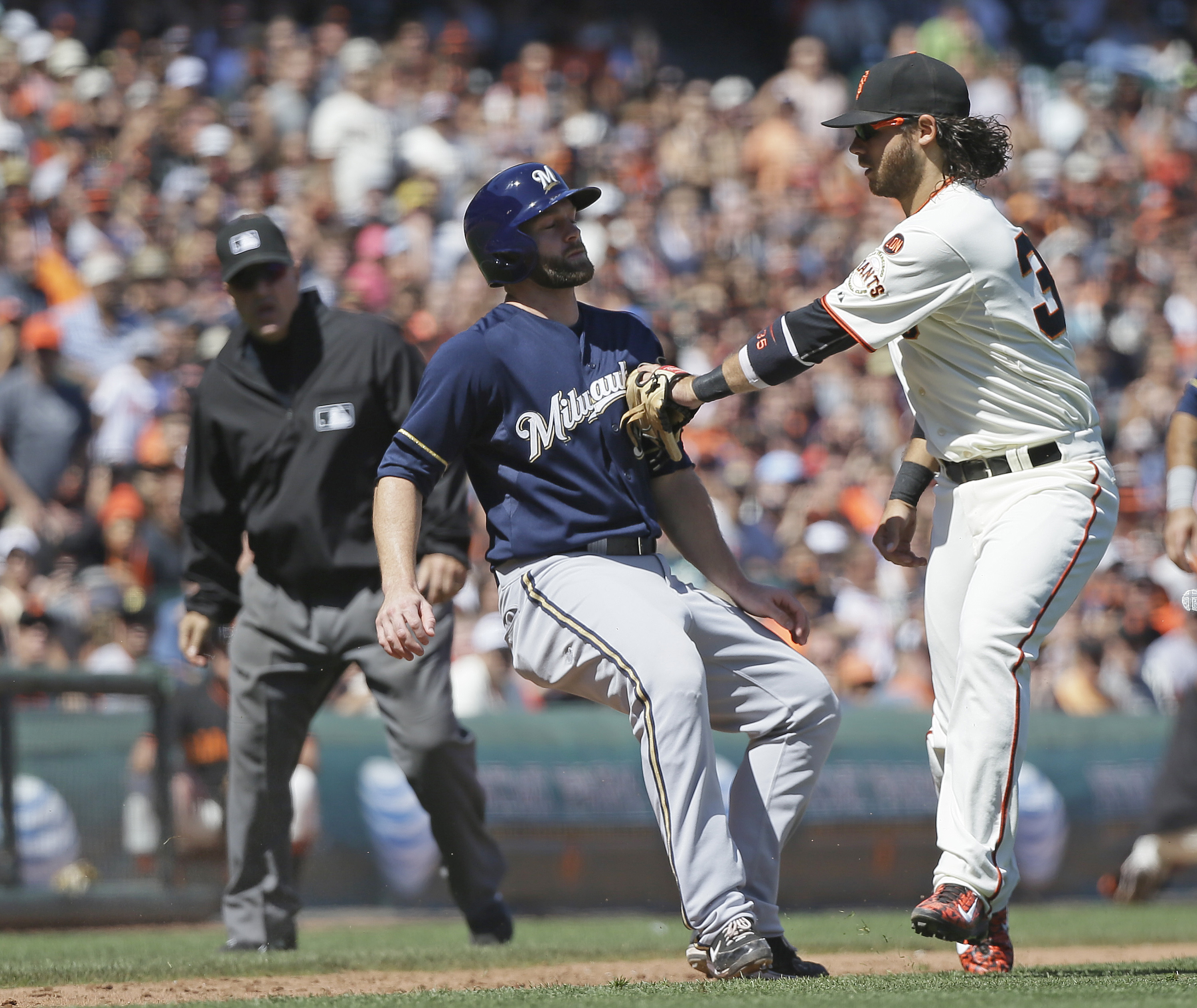 Milwaukee Brewers' Shane Peterson, left, is tagged out by San Francisco Giants shortstop Brandon Crawford on a rundown between home plate and third base on a fielder's choice in the eighth inning of a baseball game, Wednesday, July 29, 2015, in San Franci