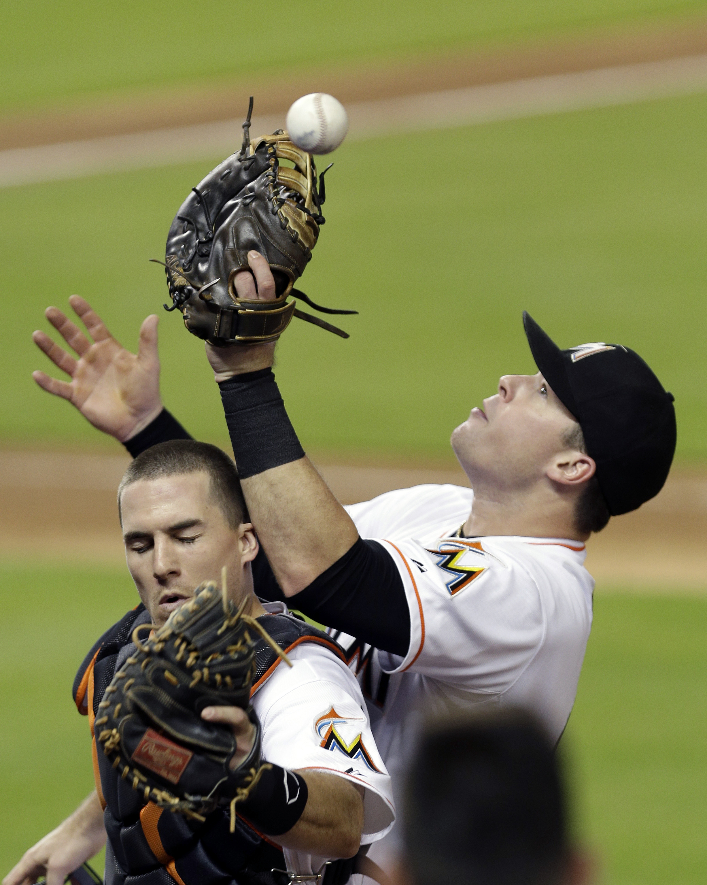 Miami Marlins catcher J.T. Realmuto, left, and first baseman Justin Bour, right, are unable to catch a foul ball hit by Washington Nationals' Yunel Escobar in the third inning of a baseball game, Wednesday, July 29, 2015, in Miami. (AP Photo/Alan Diaz)
