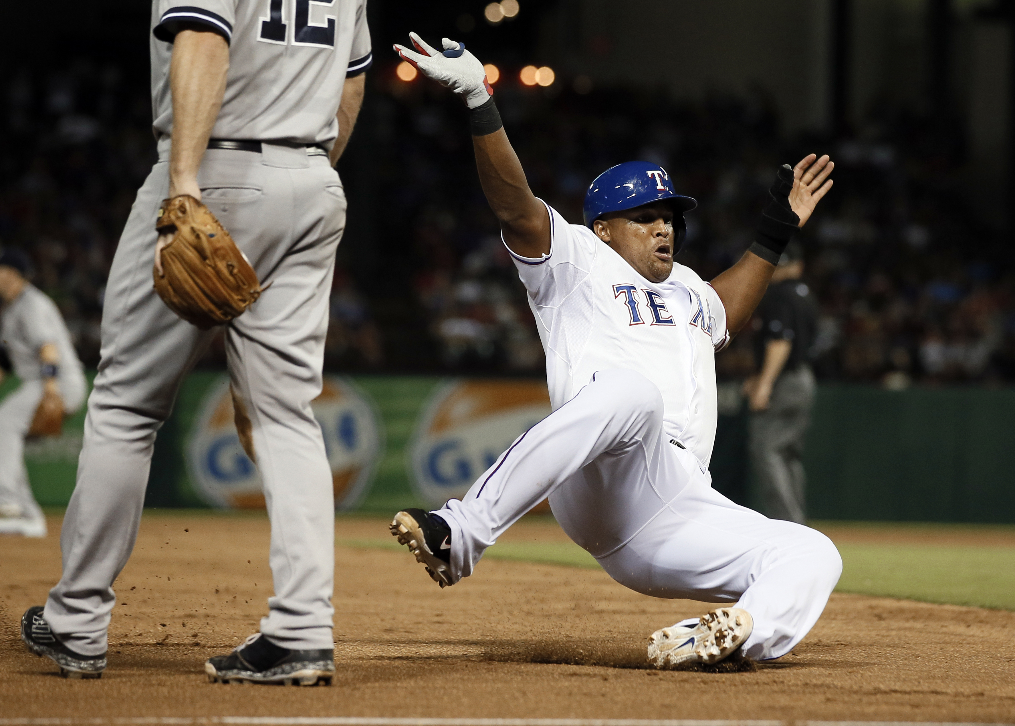 New York Yankees' Chase Headley (12) stands by the bag as Texas Rangers' Adrian Beltre, right, advances to third on a single by Mitch Moreland in the fifth inning of a baseball game Wednesday, July 29, 2015, in Arlington, Texas. (AP Photo/Tony Gutierrez)