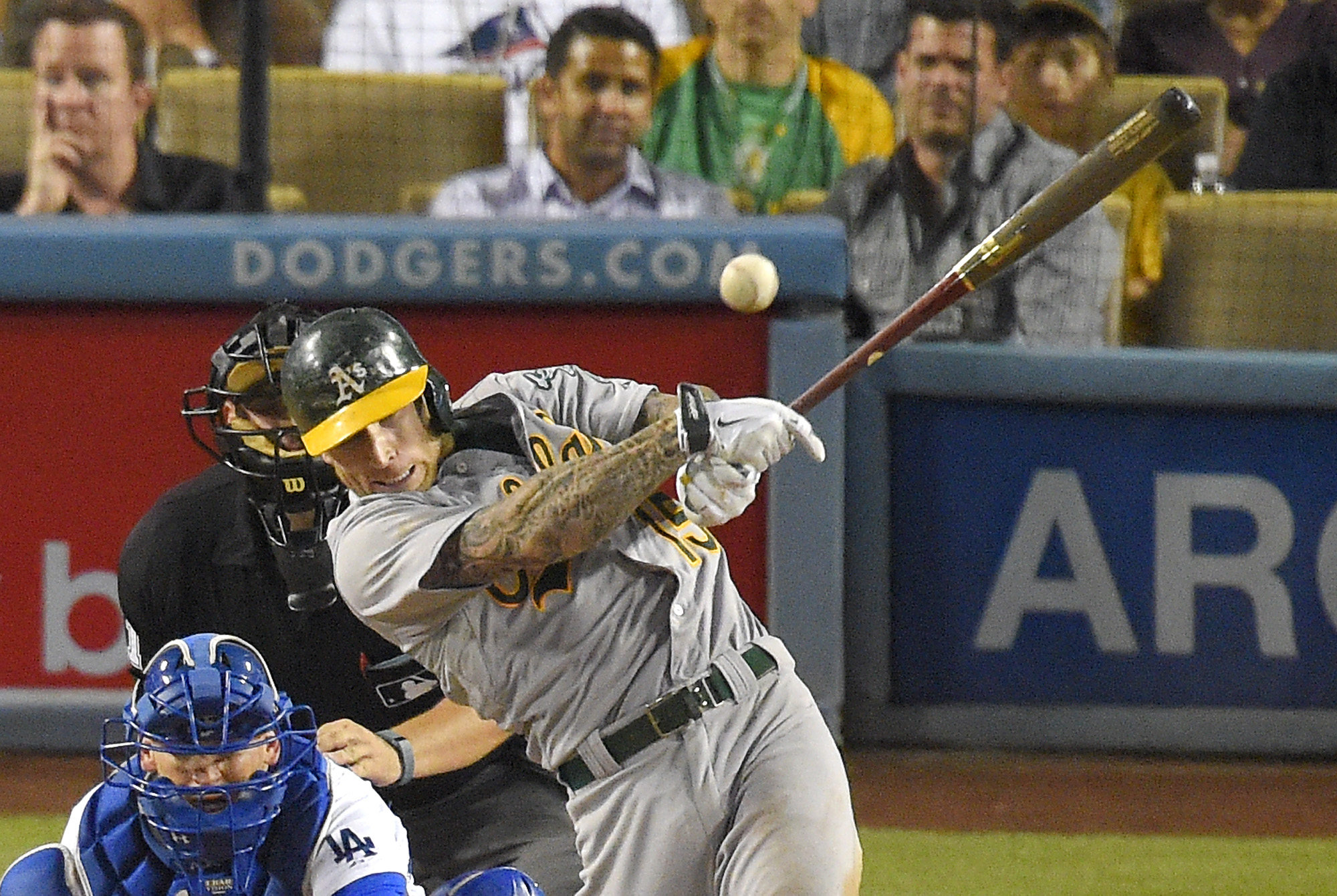 Oakland Athletics' Brett Lawrie, right, hits a two RBI single as Los Angeles Dodgers catcher Yasmani Grandal, left, and home plate umpire Brian Knight watches during the seventh inning of a baseball game, Wednesday, July 29, 2015, in Los Angeles. (AP Phot