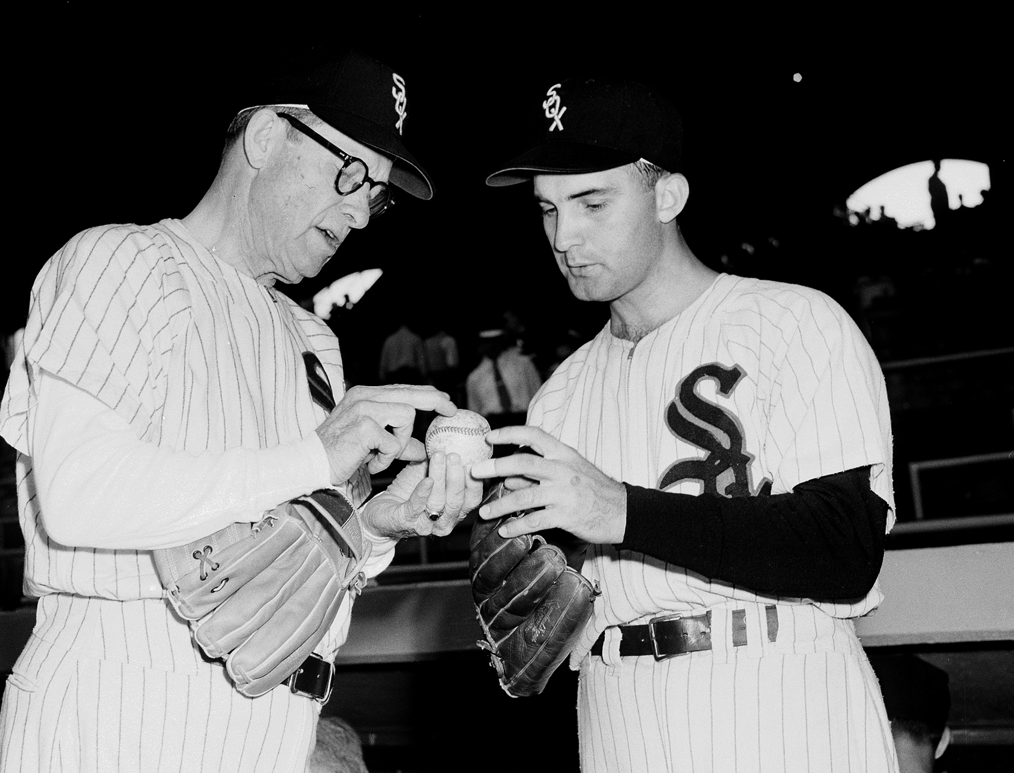 FILE - In this Aug. 10, 1954 file photo, Chicago White Sox pitcher Billy Pierce, right, compares grips with former White Sox Ed Walsh, 73, as an all-star team of White Sox old timers gathered to play an exhibition game before a White Sox-Baltimore Orioles