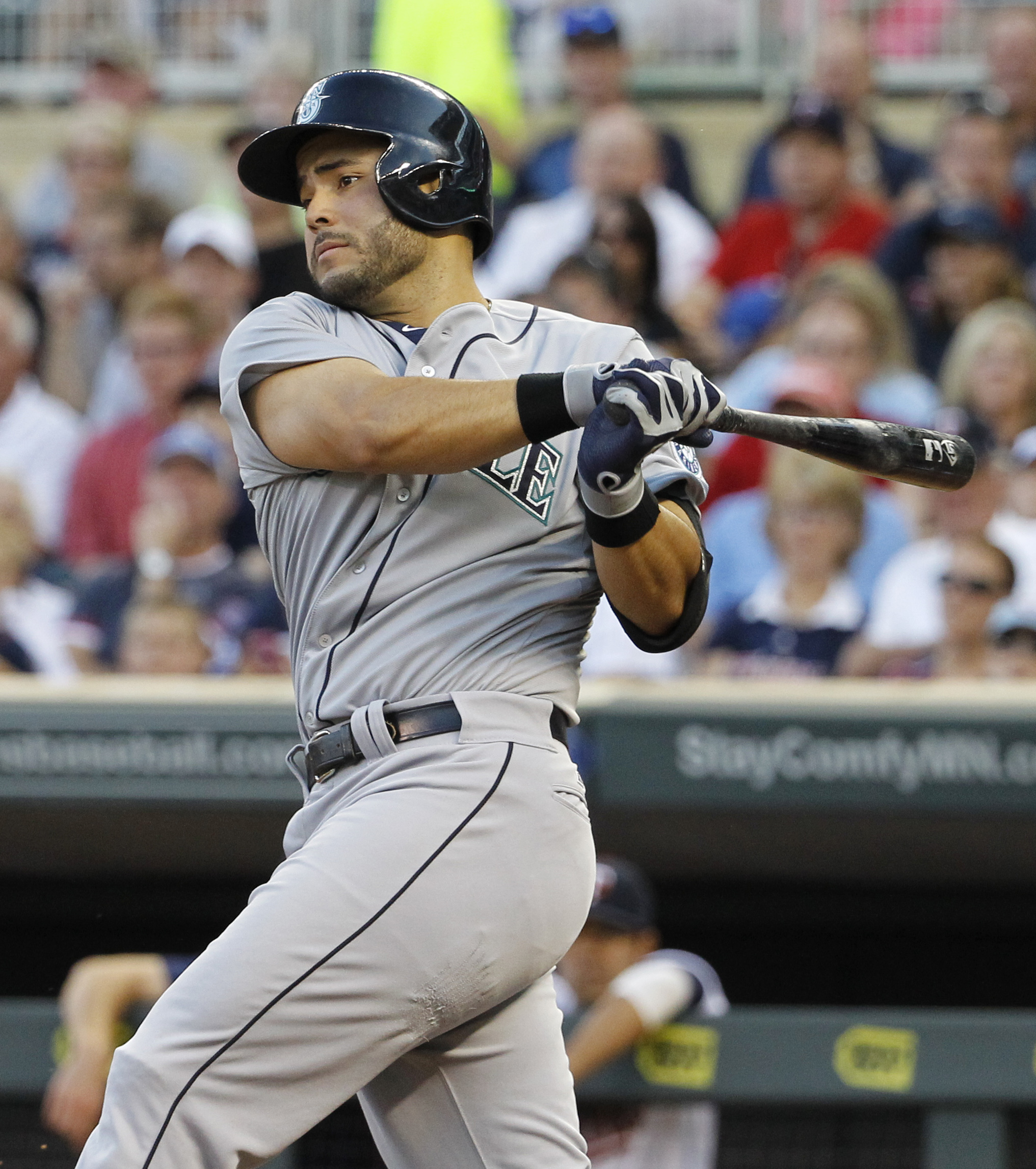 Seattle Mariners' Jesus Montero follows through on and RBI double off Minnesota Twins starting pitcher Tommy Milone during the fourth inning of a baseball game in Minneapolis, Friday, July 31, 2015. (AP Photo/Ann Heisenfelt)