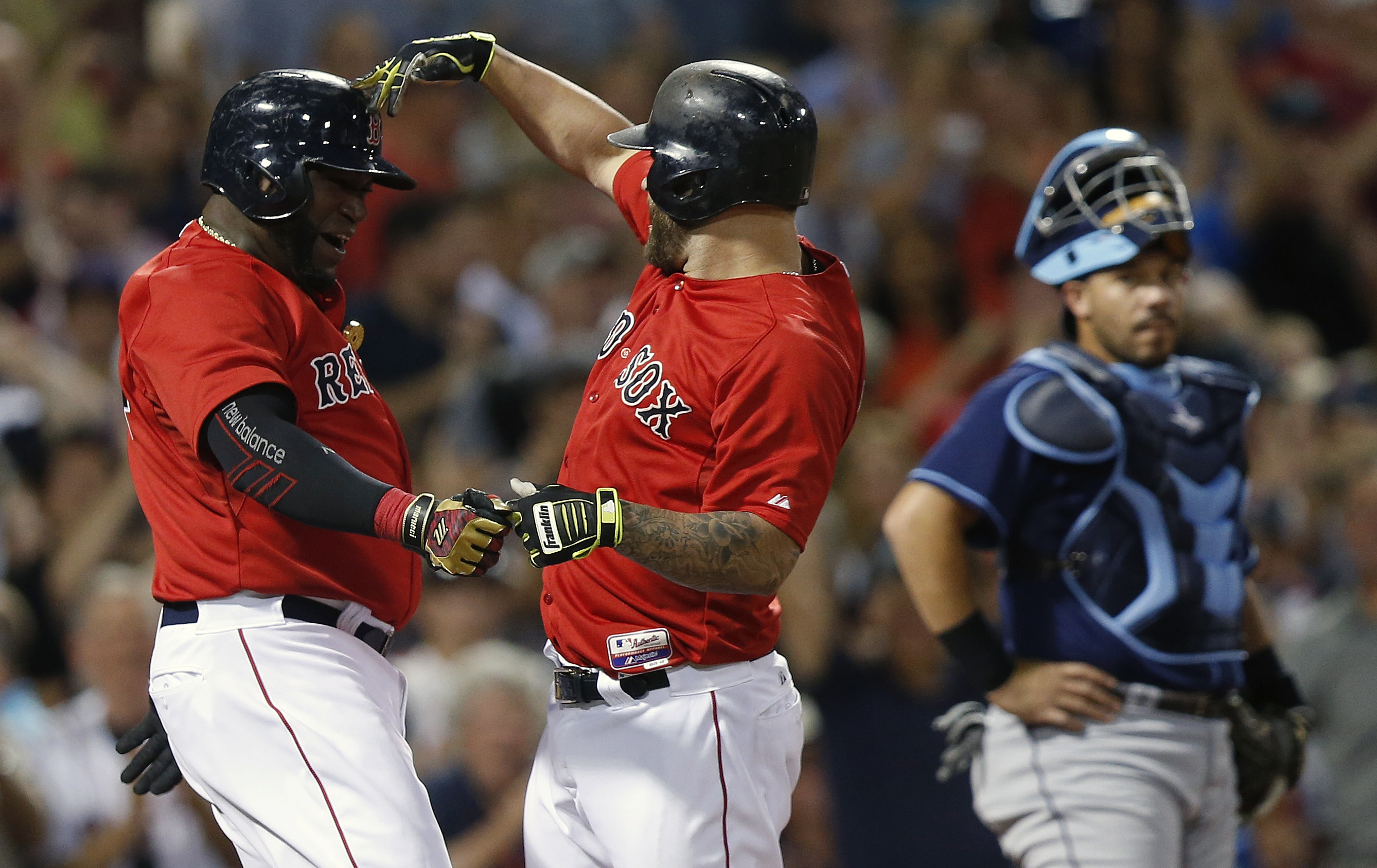 Boston Red Sox's Mike Napoli, center, celebrates his two-run home run that also drove in David Ortiz, left, as Tampa Bay Rays' Curt Casali, right, looks on during the seventh inning of a baseball game in Boston, Friday, July 31, 2015. (AP Photo/Michael Dw