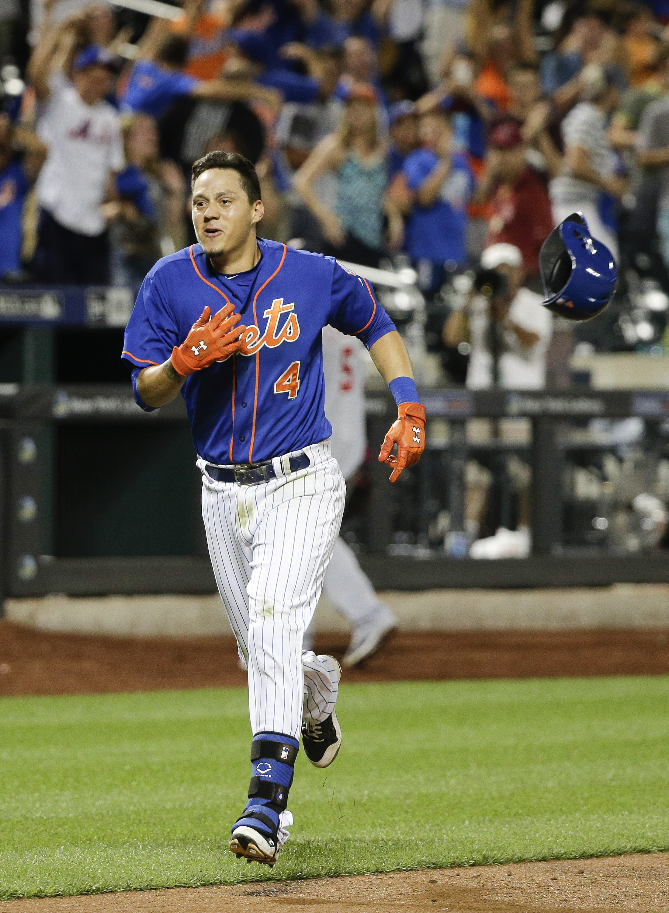 New York Mets' Wilmer Flores (4) tosses his helmet aside as he heads for home after hitting a walk off solo home run during the twelfth inning of a baseball game to beat the Washington Nationals 2-1, Friday, July 31, 2015, in New York. (AP Photo/Julie Jac