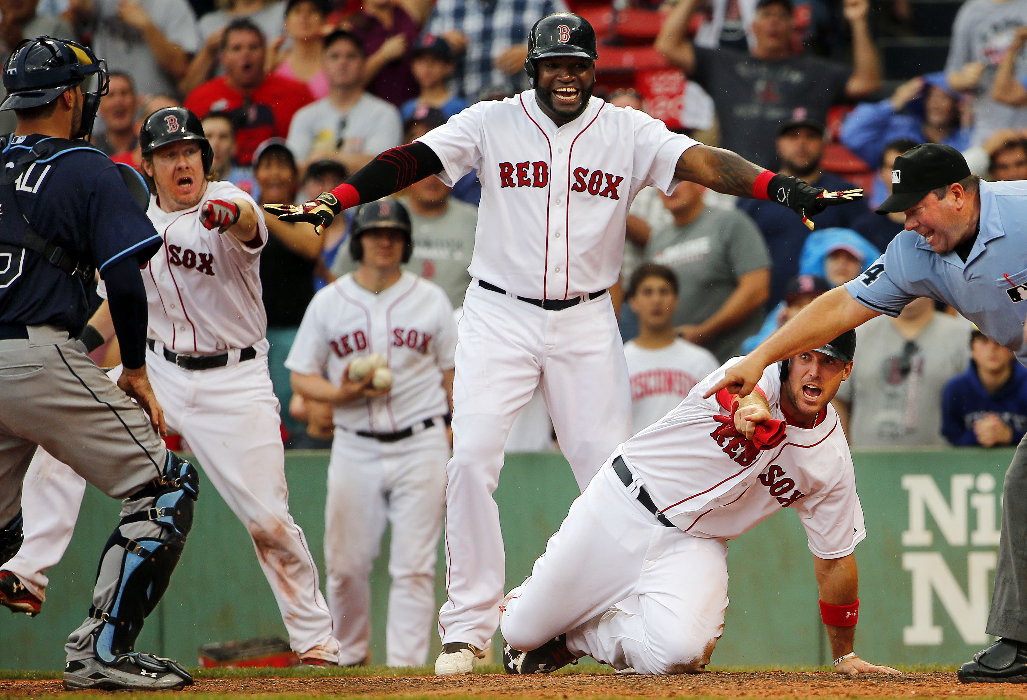 Boston Red Sox's Ryan Hanigan, second from left, David Ortiz, center, and Travis Shaw, second from right, along with umpire Sam Holbrook, right, all signal safe after Shaw slid around the tag of Tampa Bay Rays catcher Curt Casali, left, during the sixth i