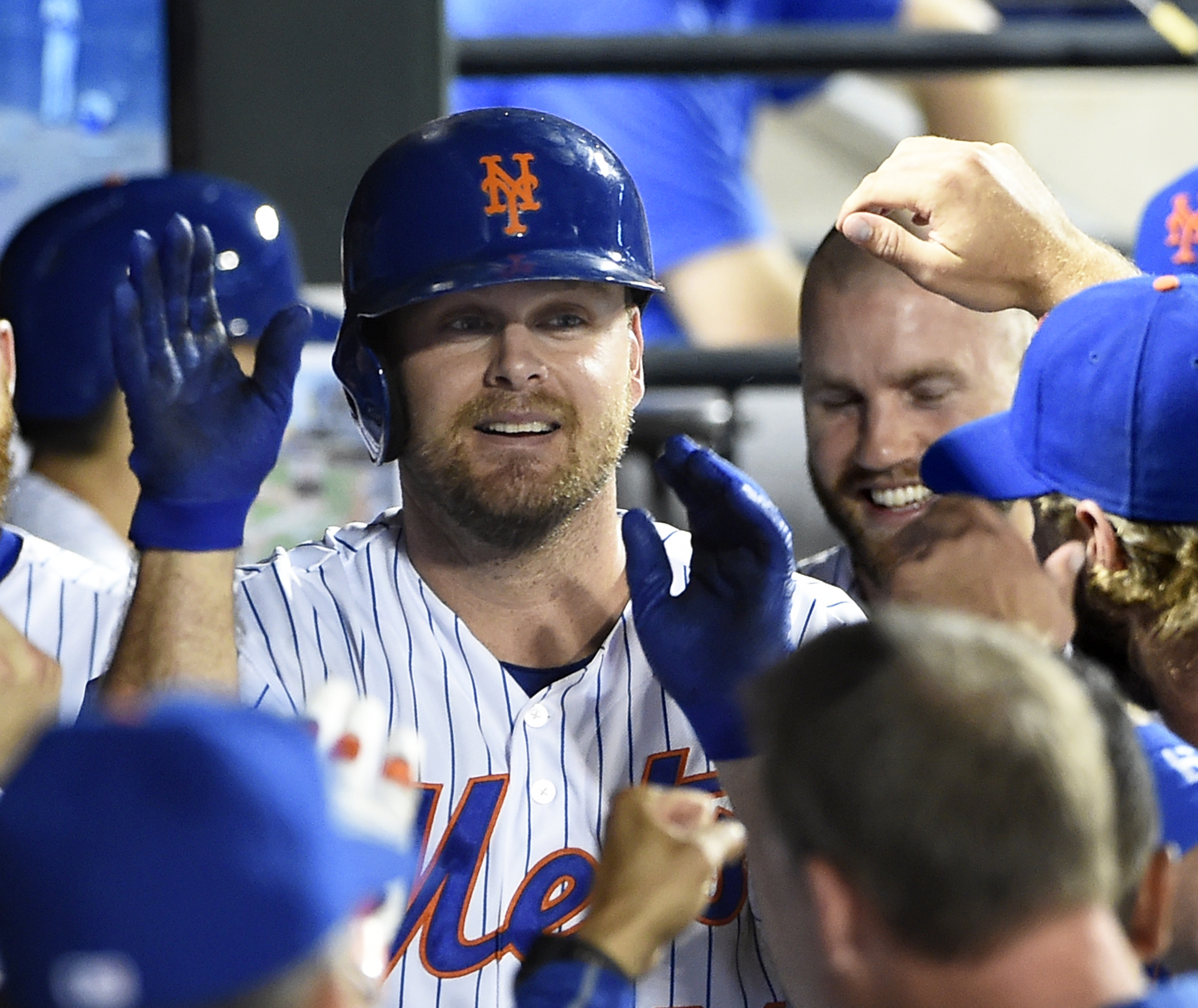 New York Mets' Lucas Duda is congratulated by teammates in the dugout after hitting his second home run of a baseball game against the Washington Nationals in the seventh inning at Citi Field on Saturday, Aug. 1, 2015, in New York. (AP Photo/Kathy Kmonice
