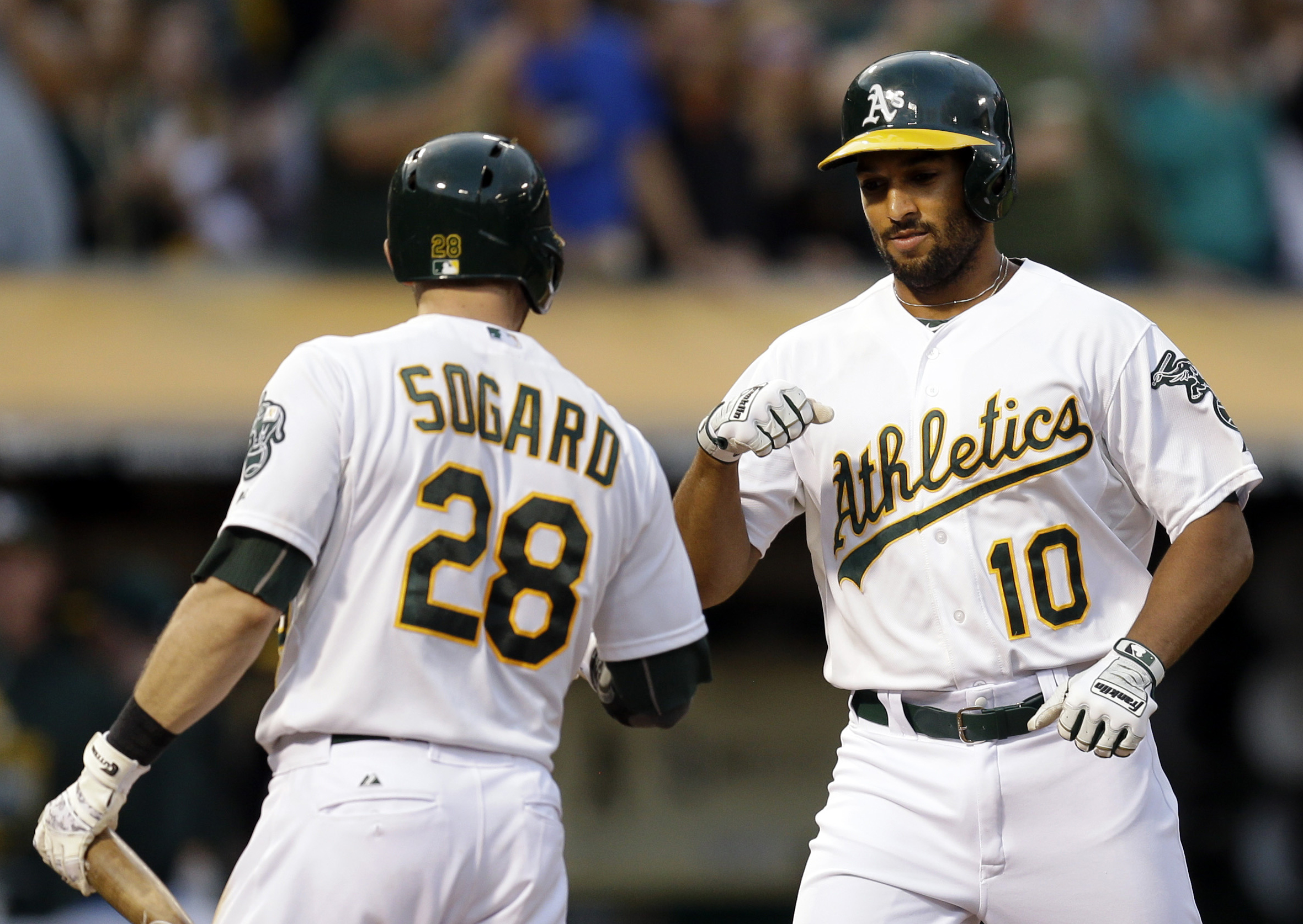 Oakland Athletics' Marcus Semien, right, is congratulated by teammate Eric Sogard (28) after hitting a home run off Cleveland Indians' Cody Anderson in the seventh inning of a baseball game Saturday, Aug. 1, 2015, in Oakland, Calif. (AP Photo/Ben Margot)
