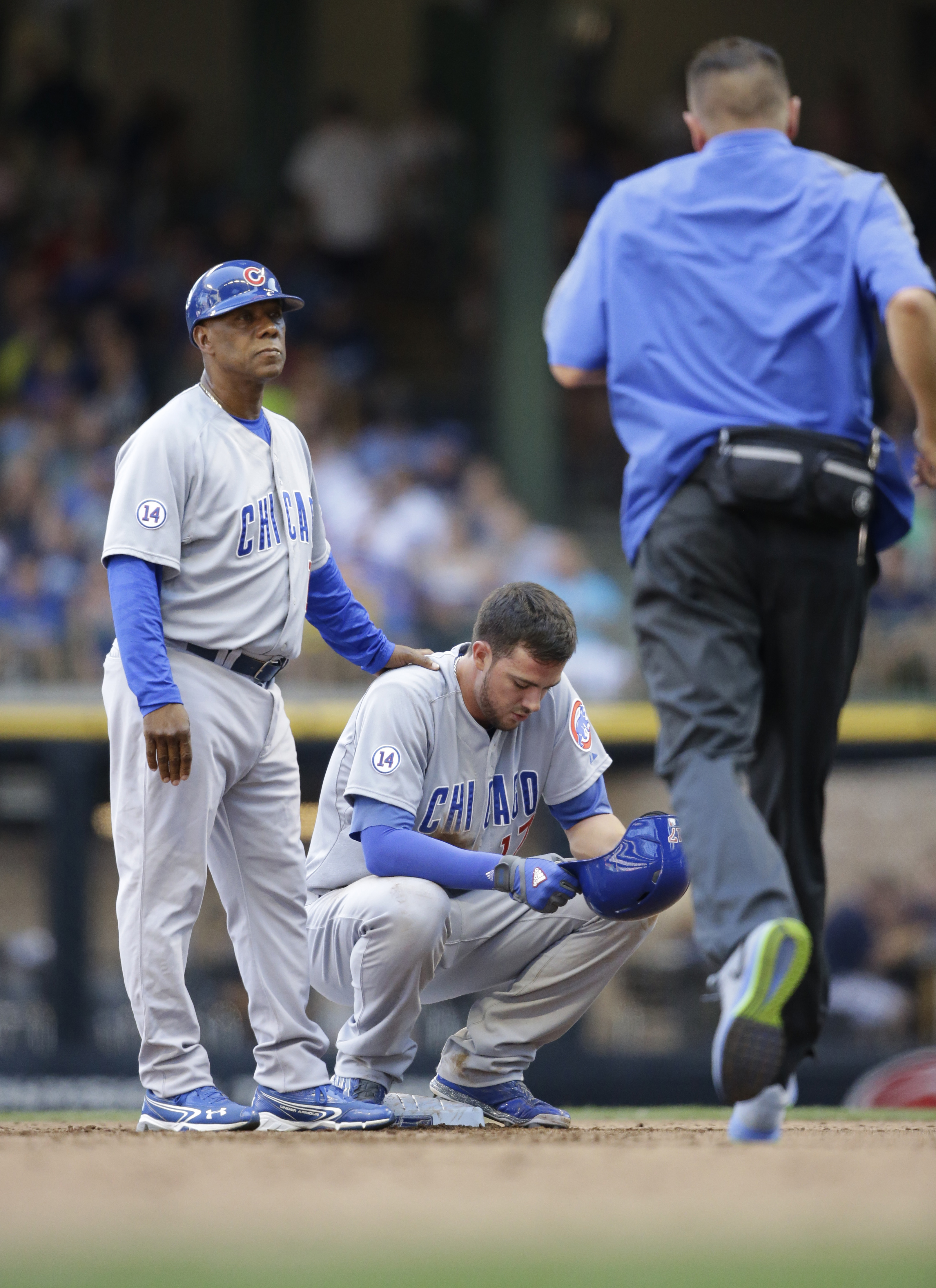 Chicago Cubs' Kris Bryant, center, reacts at second base with third base coach Gary Jones, left, as a trainer runs to his aid during the fifth inning of a baseball game against the Milwaukee Brewers, Sunday, Aug. 2, 2015, in Milwaukee. Bryant was hurt on