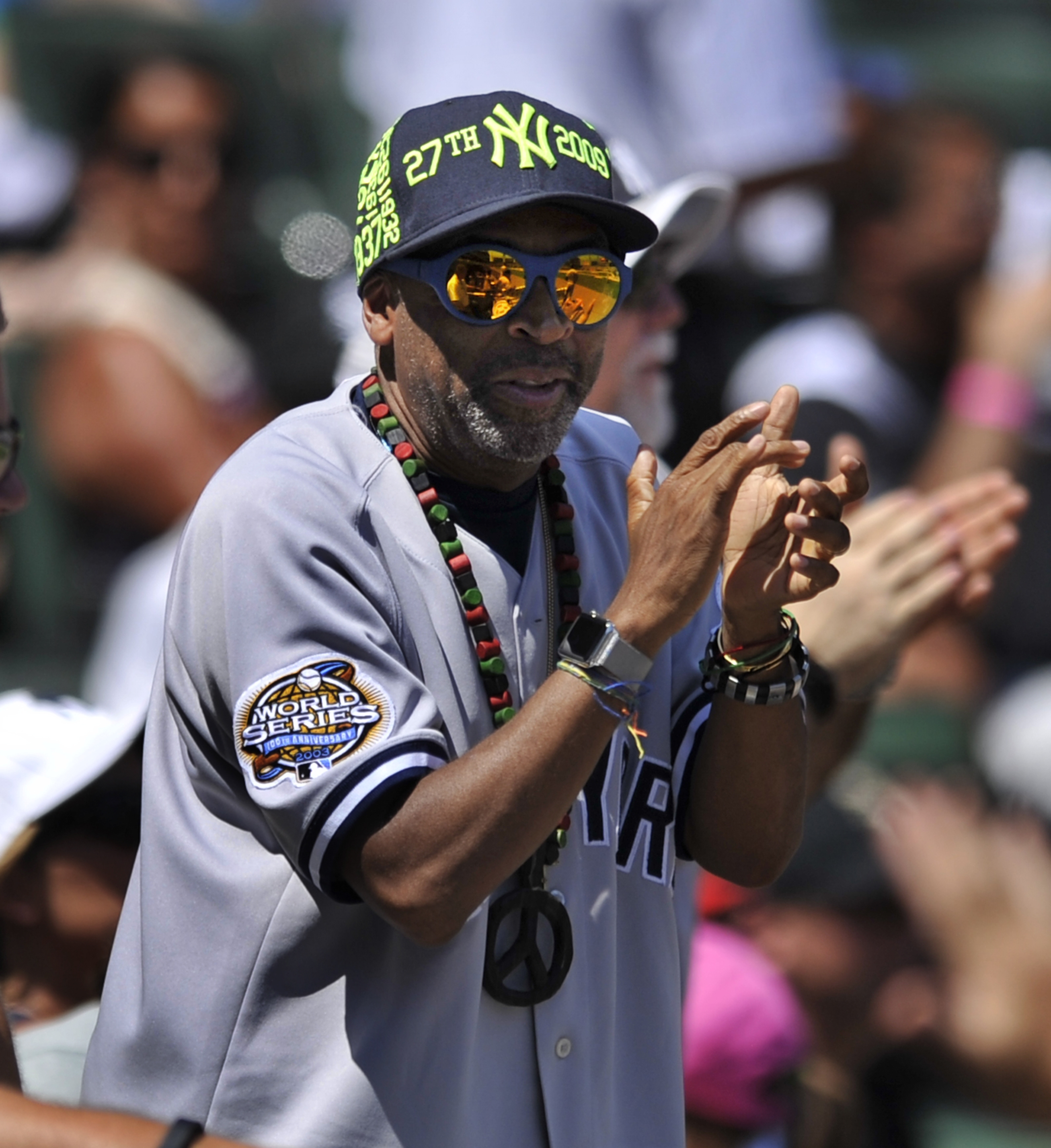 Director Spike Lee celebrates after New York Yankees' Brian McCann and Carlos Beltran scored on a Didi Gregorius single during the fourth inning of a baseball game against the Chicago White Sox, Sunday, Aug 2, 2015, in Chicago. (AP Photo/Paul Beaty)
