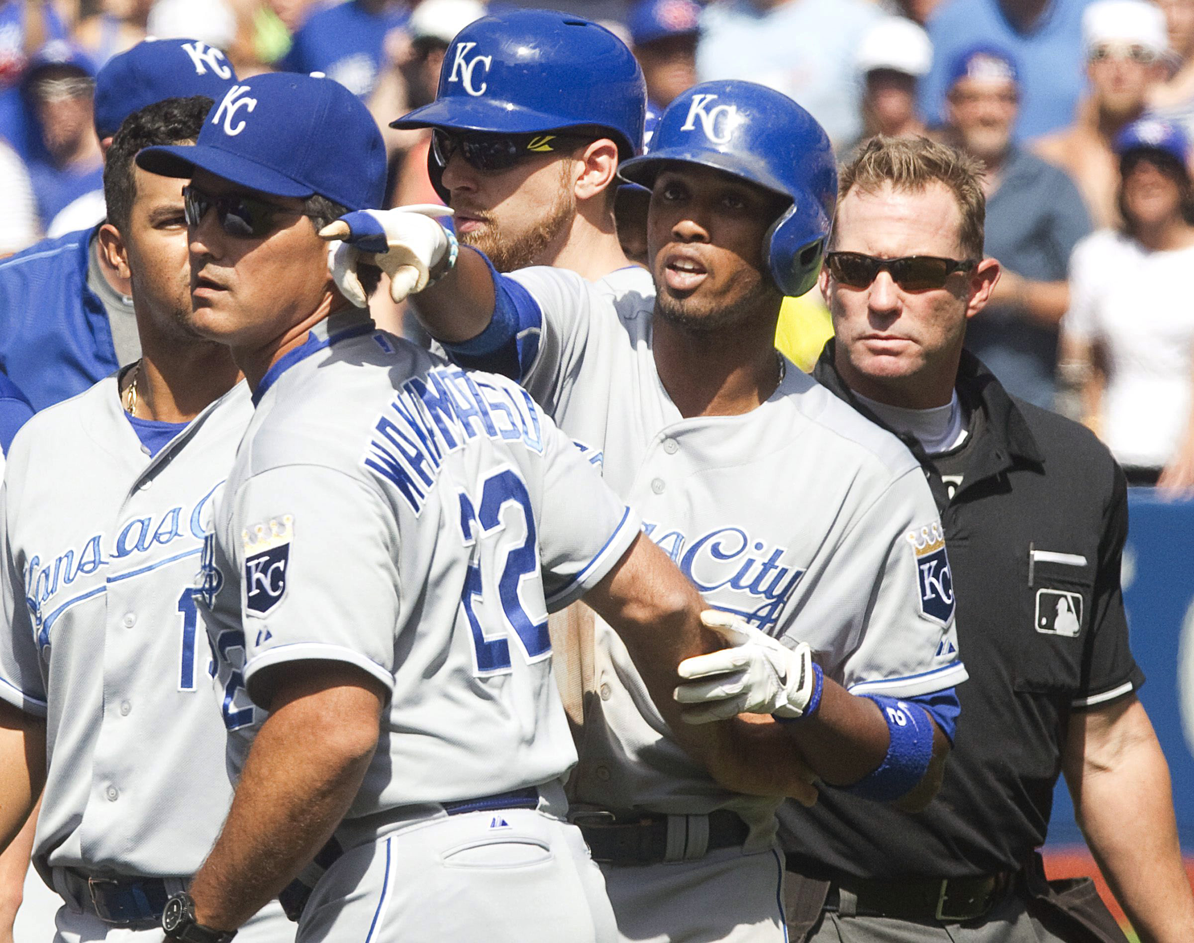 Kansas City Royals Alcides Escobar is held back by coach Don Wakamatsu (22) as he gestures at Toronto Blue Jays pitcher Aaron Sanchez who was ejected from their baseball game in Toronto for hitting Escobar on Sunday Aug. 2, 2015. Home plate umpire Jim Wol