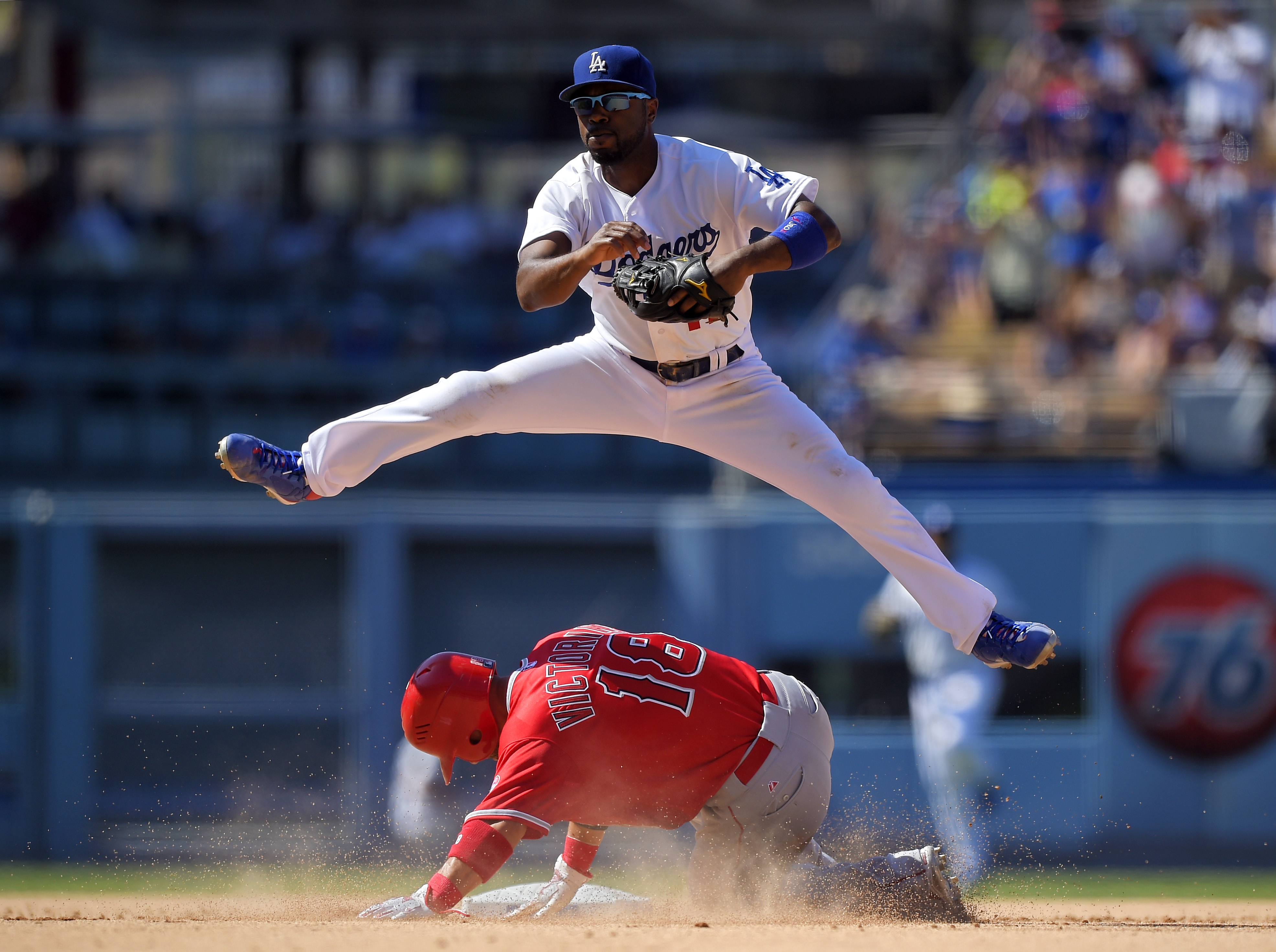 Los Angeles Angels Shane Victorino, below, is forced out at second as Los Angeles Dodgers shortstop Jimmy Rollins attempts to throw out Erick Aybar at first during the ninth inning of a baseball game, Sunday, Aug. 2, 2015, in Los Angeles. Aybar was safe a