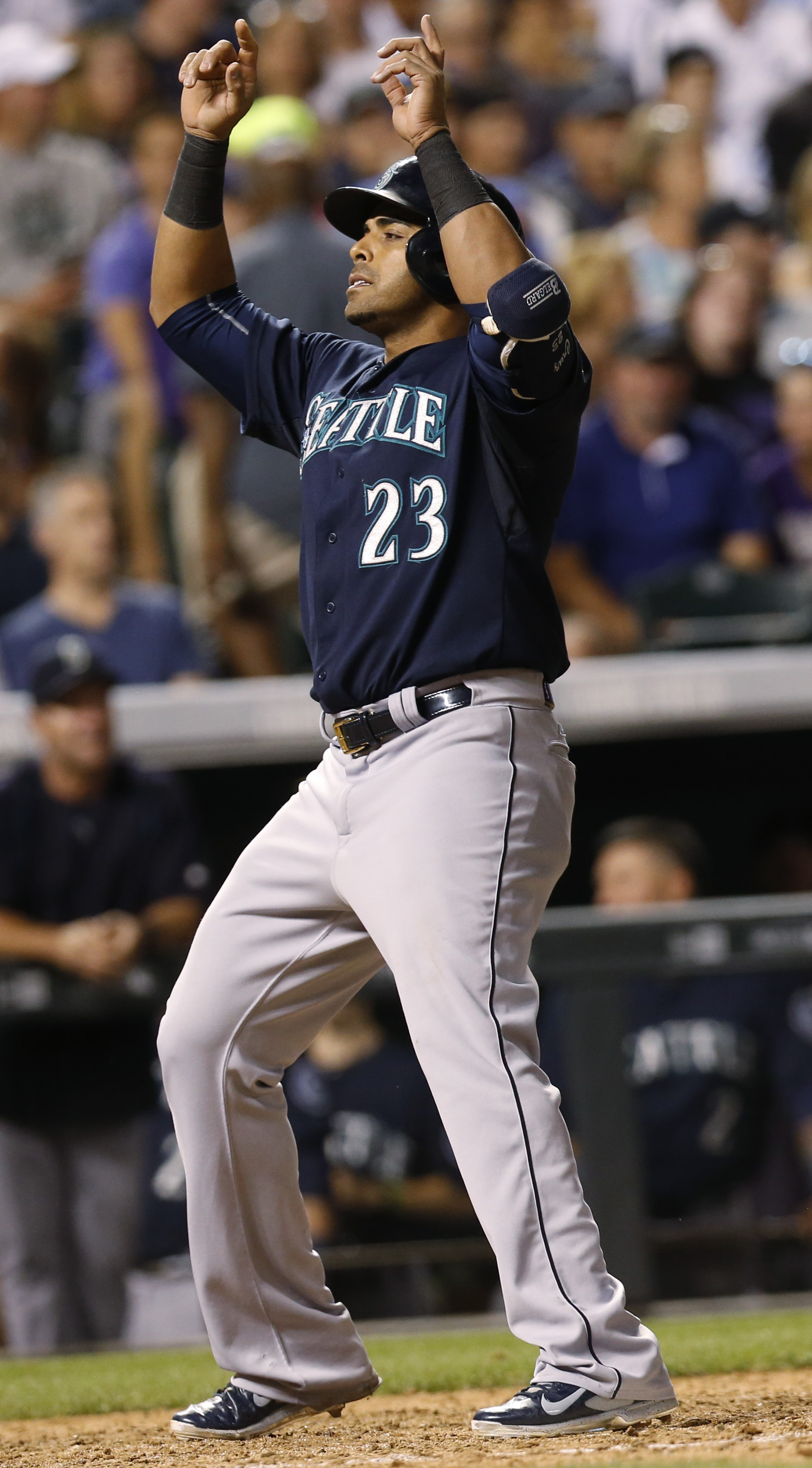 Seattle Mariners' Nelson Cruz gestures as he crosses home plate after hitting a solo home run off Colorado Rockies relief pitcher Scott Oberg to lead off the seventh inning of a baseball game Tuesday, Aug. 4, 2015, in Denver. (AP Photo/David Zalubowski)