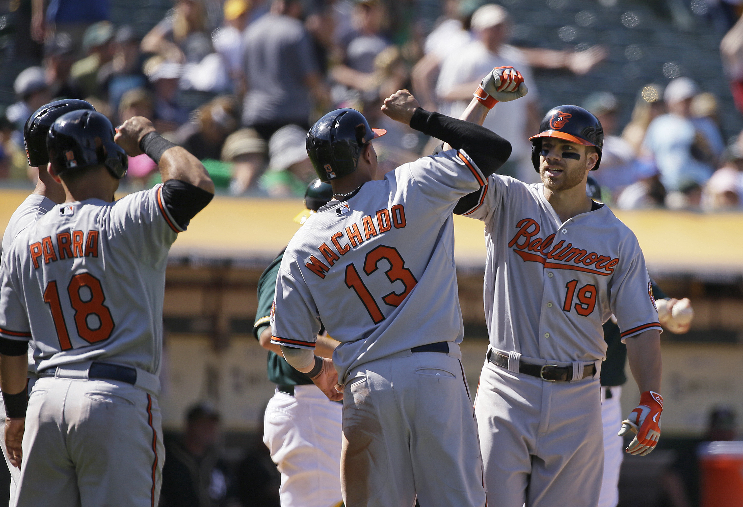 Baltimore Orioles' Chris Davis, right, is greeted by teammates Gerardo Parra, left, and Manny Machado, center, after hitting a grand slam off Oakland Athletics relief pitcher Arnold Leon during the 10th inning of a baseball game Wednesday, Aug. 5, 2015, i