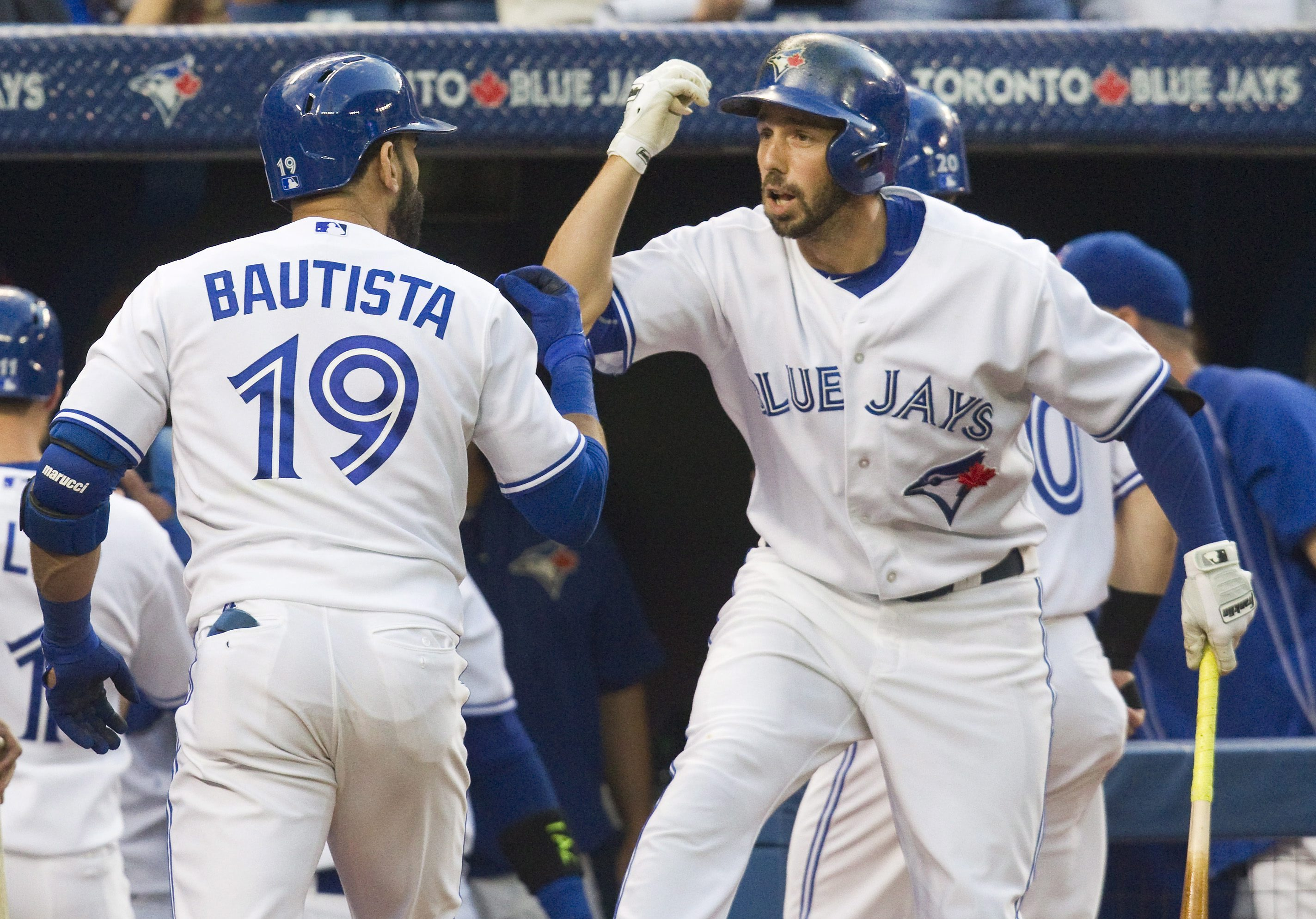 Toronto Blue Jays' Chris Colabello congratulates Jose Bautista after Bautista hit a grand slam against the Minnesota Twins during the second inning of a baseball game Wednesday, Aug. 5, 2015, in Toronto. (Fred Thornhill/The Canadian Press via AP)