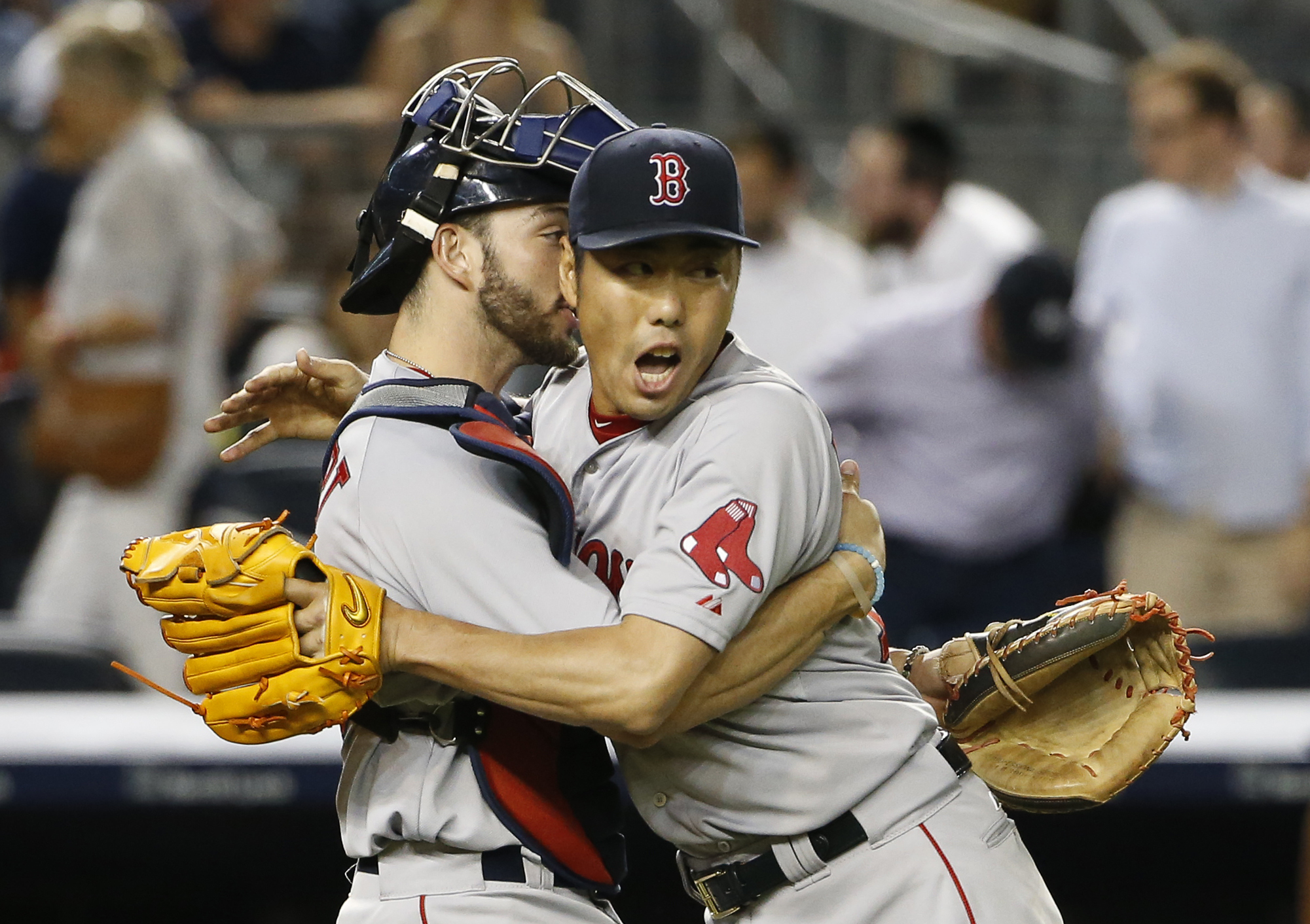 Boston Red Sox catcher Blake Swihart, left, embraces Red Sox relief pitcher Koji Uehara after Uehara earned the save in a 2-1 victory over the New York Yankees in a baseball game at Yankee Stadium in New York, Wednesday, Aug. 5, 2015. (AP Photo/Kathy Will
