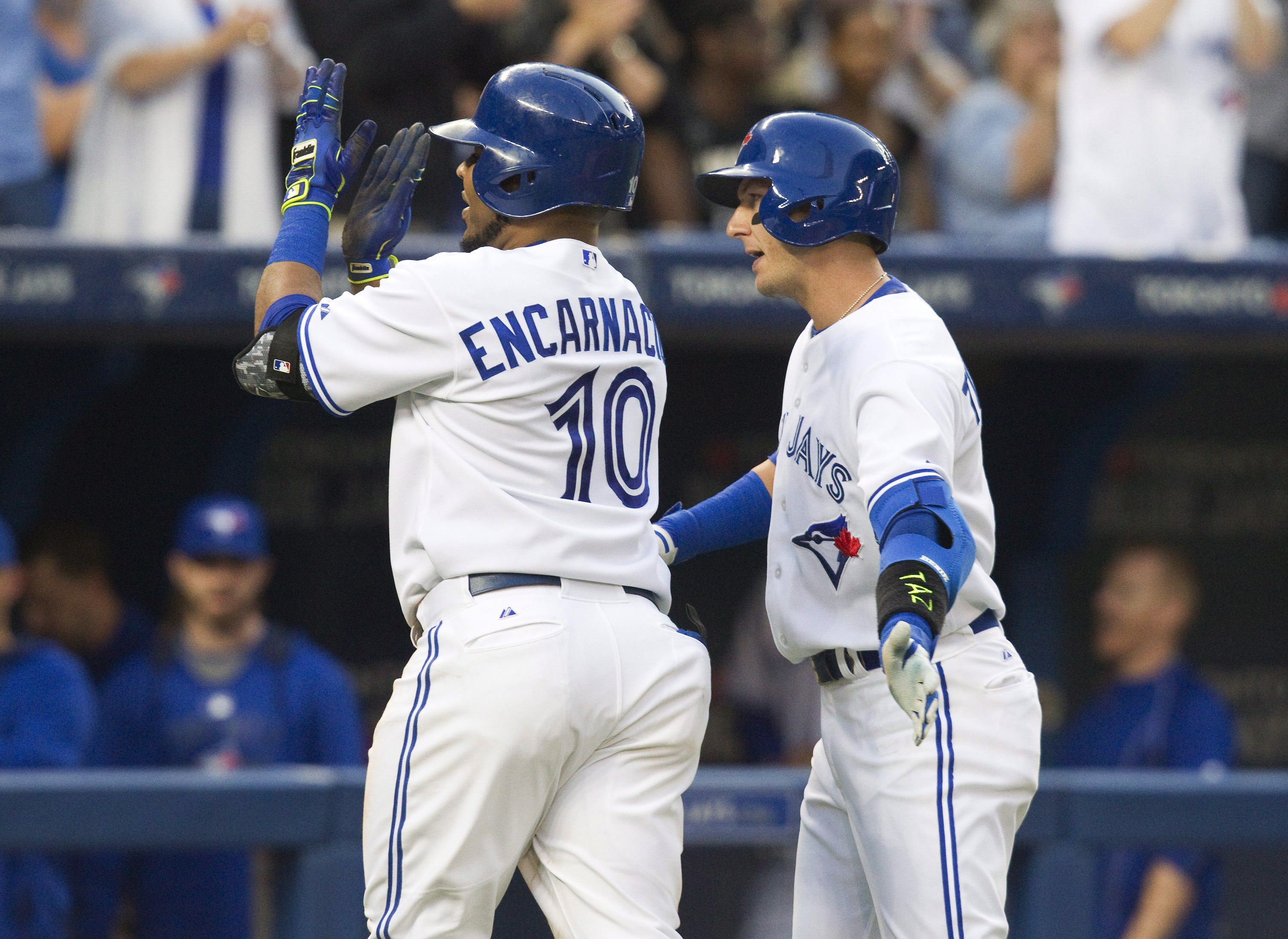 Toronto Blue Jays' Edwin Encarnacion, left, is greeted by teammate Troy Tulowitzki after hitting a two-run home run during the third inning of a baseball game against the Minnesota Twins on Thursday, Aug. 6, 2015, in Toronto. (Fred Thornhill/The Canadian