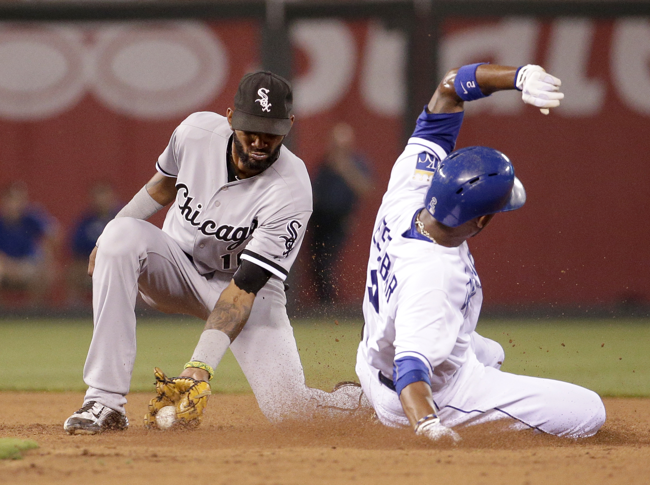 Kansas City Royals' Alcides Escobar, right, beats the tag by Chicago White Sox shortstop Alexei Ramirez, left, to steal second during the seventh inning of a baseball game Friday, Aug. 7, 2015, in Kansas City, Mo. (AP Photo/Charlie Riedel)