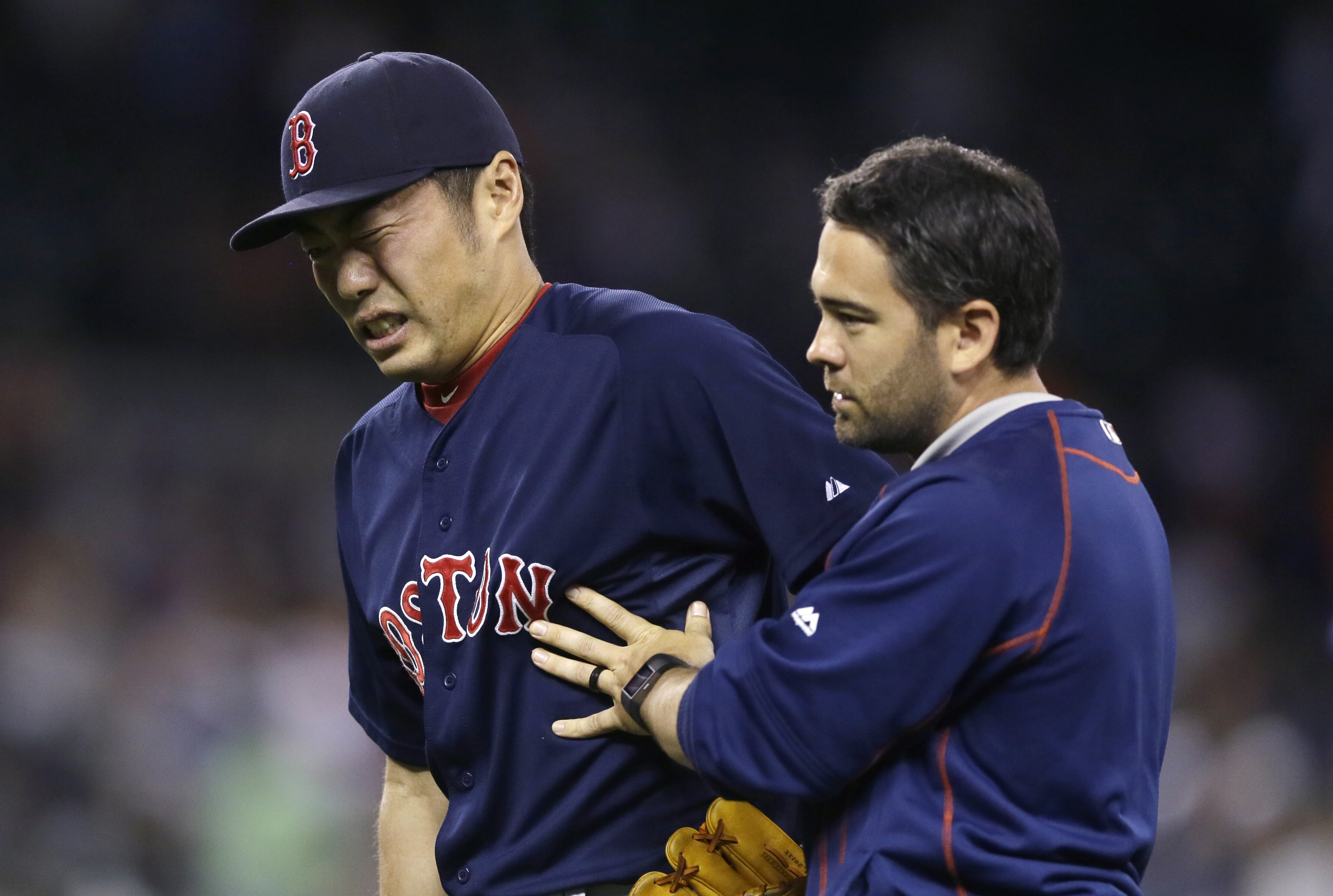 Boston Red Sox relief pitcher Koji Uehara is helped off the field after a baseball game against the Detroit Tigers, Friday, Aug. 7, 2015, in Detroit. Uehara was hit on a grounder by Tigers' Ian Kinsler. The Red Sox defeated the Tigers 7-2. (AP Photo/Carlo