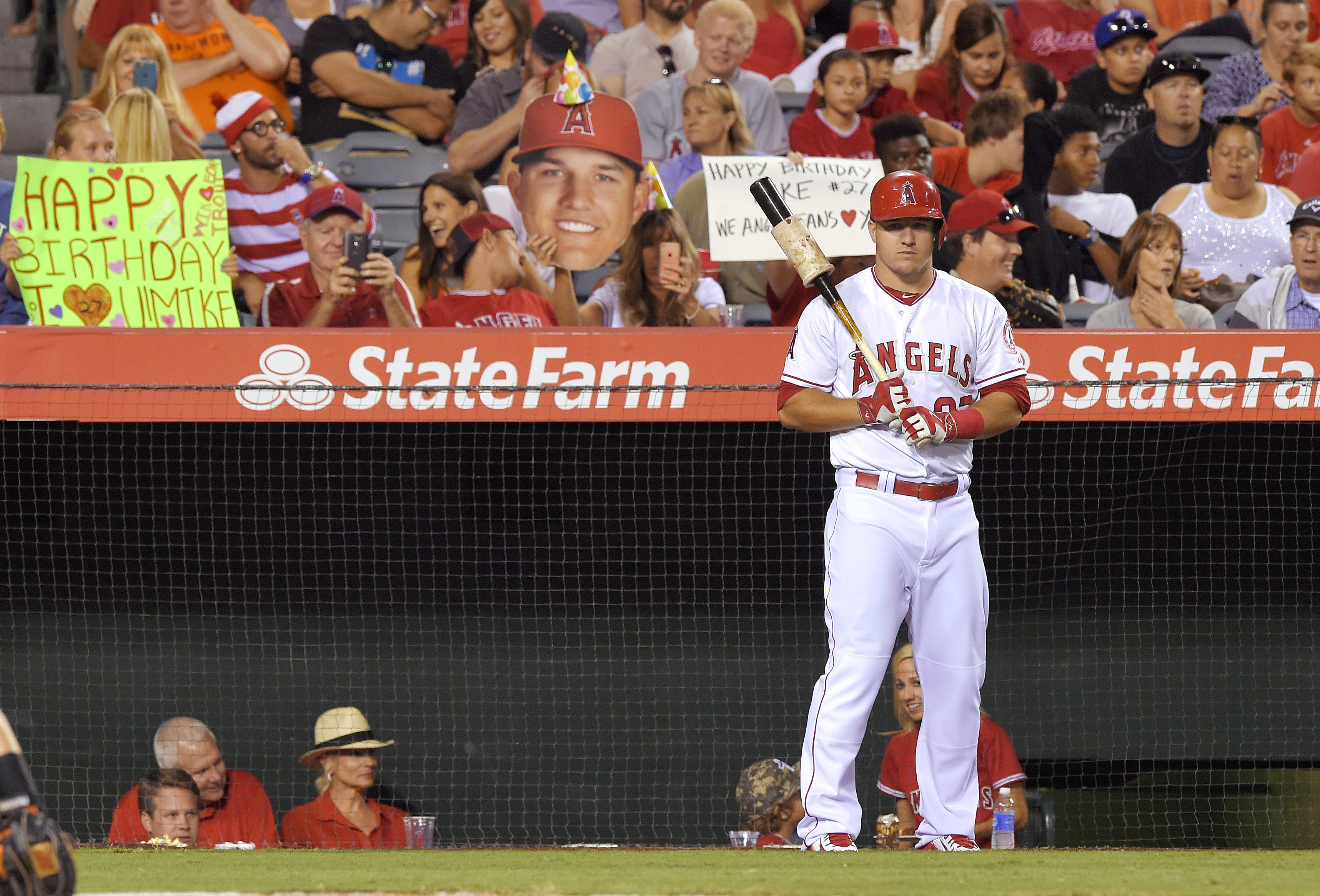 Los Angeles Angels' Mike Trout, right, gets ready to bat as fans hold up signs for his birthday during the fourth inning of the Angels' baseball game against the Baltimore Orioles, Friday, Aug. 7, 2015, in Anaheim, Calif. (AP Photo/Mark J. Terrill)