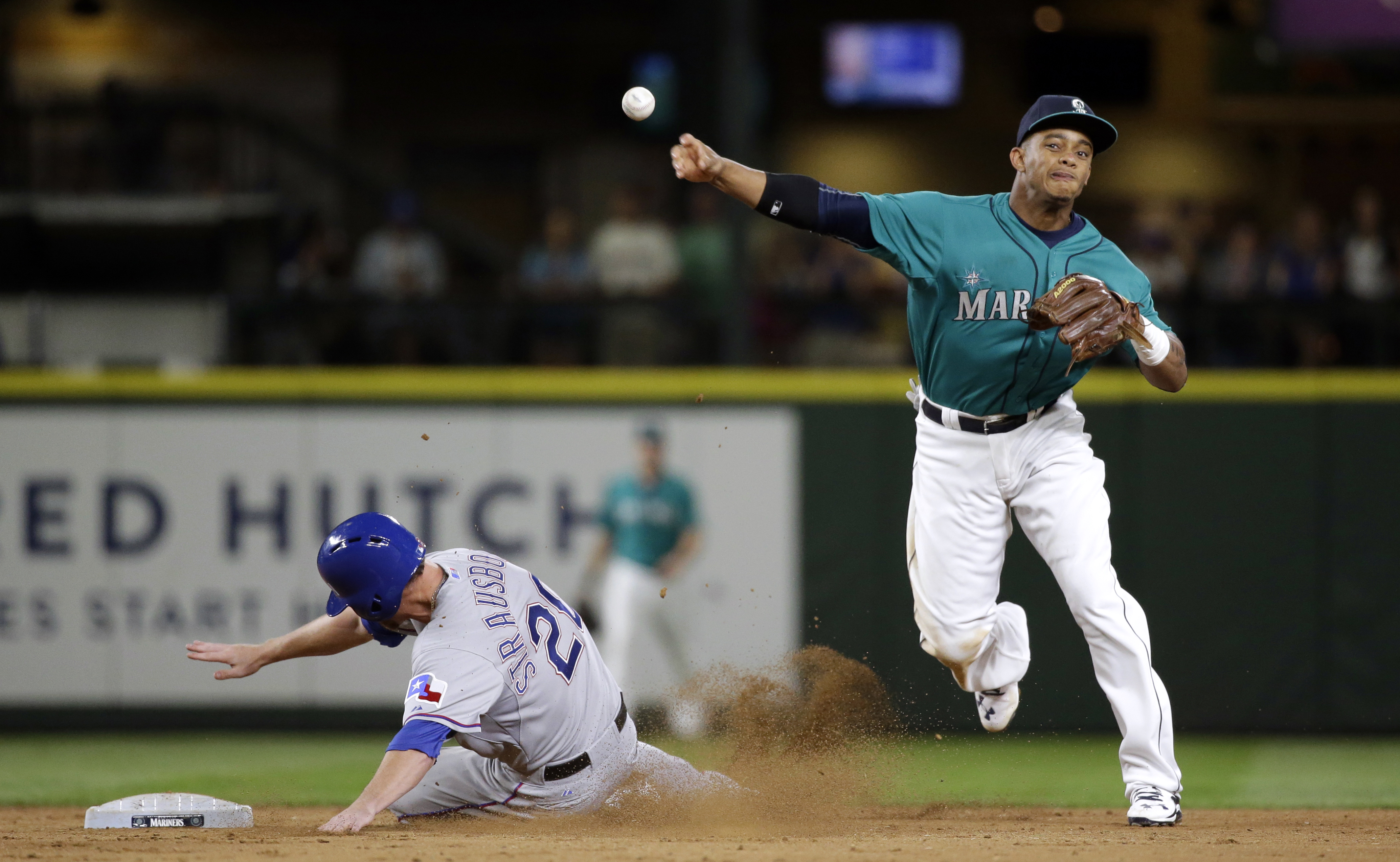 Seattle Mariners shortstop Ketel Marte, right, throws to first after forcing out Texas Rangers' Ryan Strausborger at second base during the ninth inning of a baseball game Friday, Aug. 7, 2015, in Seattle. The Mariners won 4-3. (AP Photo/Elaine Thompson)