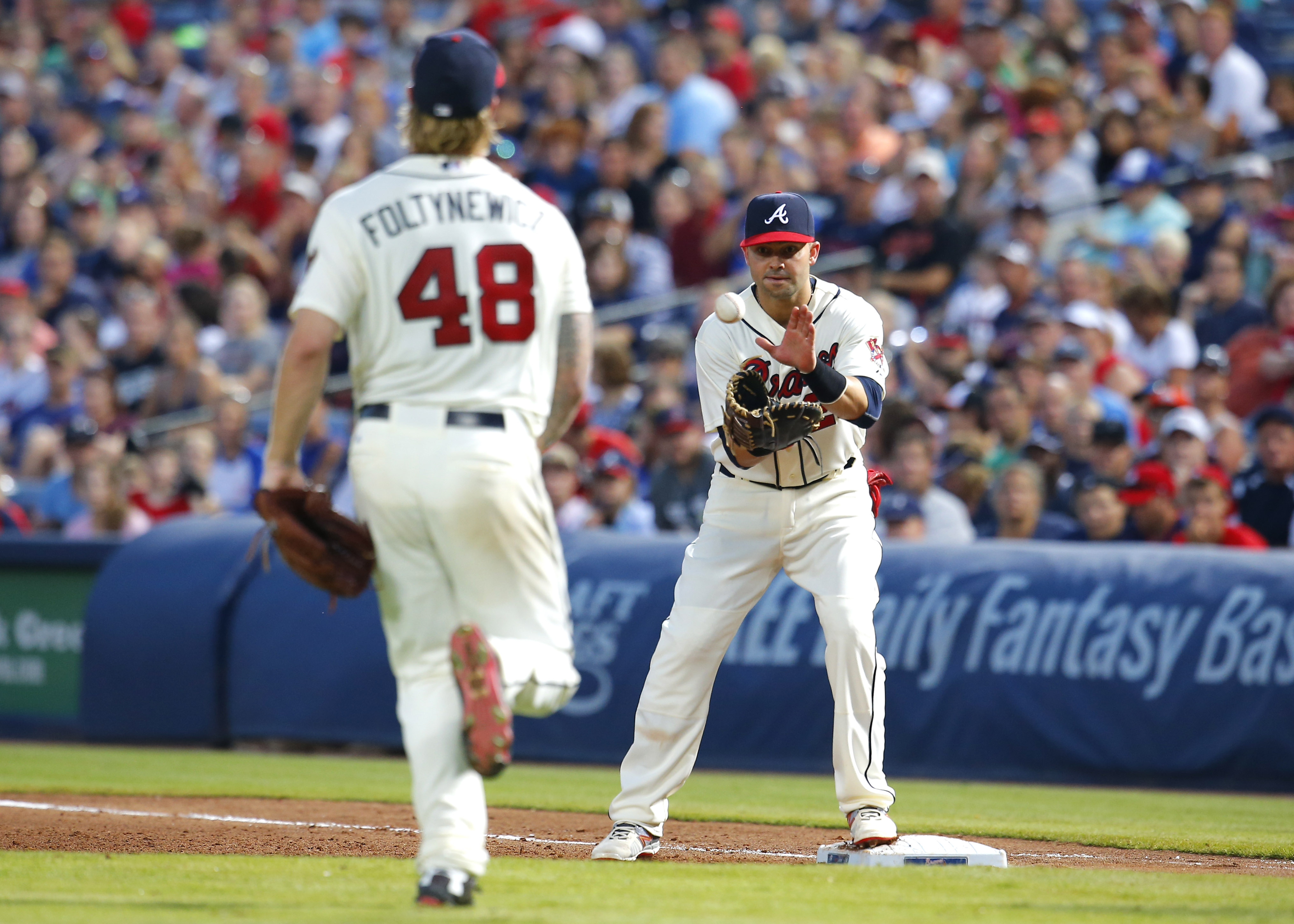 Atlanta Braves starting pitcher Mike Foltynewicz (48) tosses to first baseman Nick Swisher, right, for the out against Miami Marlins' Christian Yelich in the fifth inning of a baseball game Saturday, Aug. 8, 2015, in Atlanta. (AP Photo/Todd Kirkland)