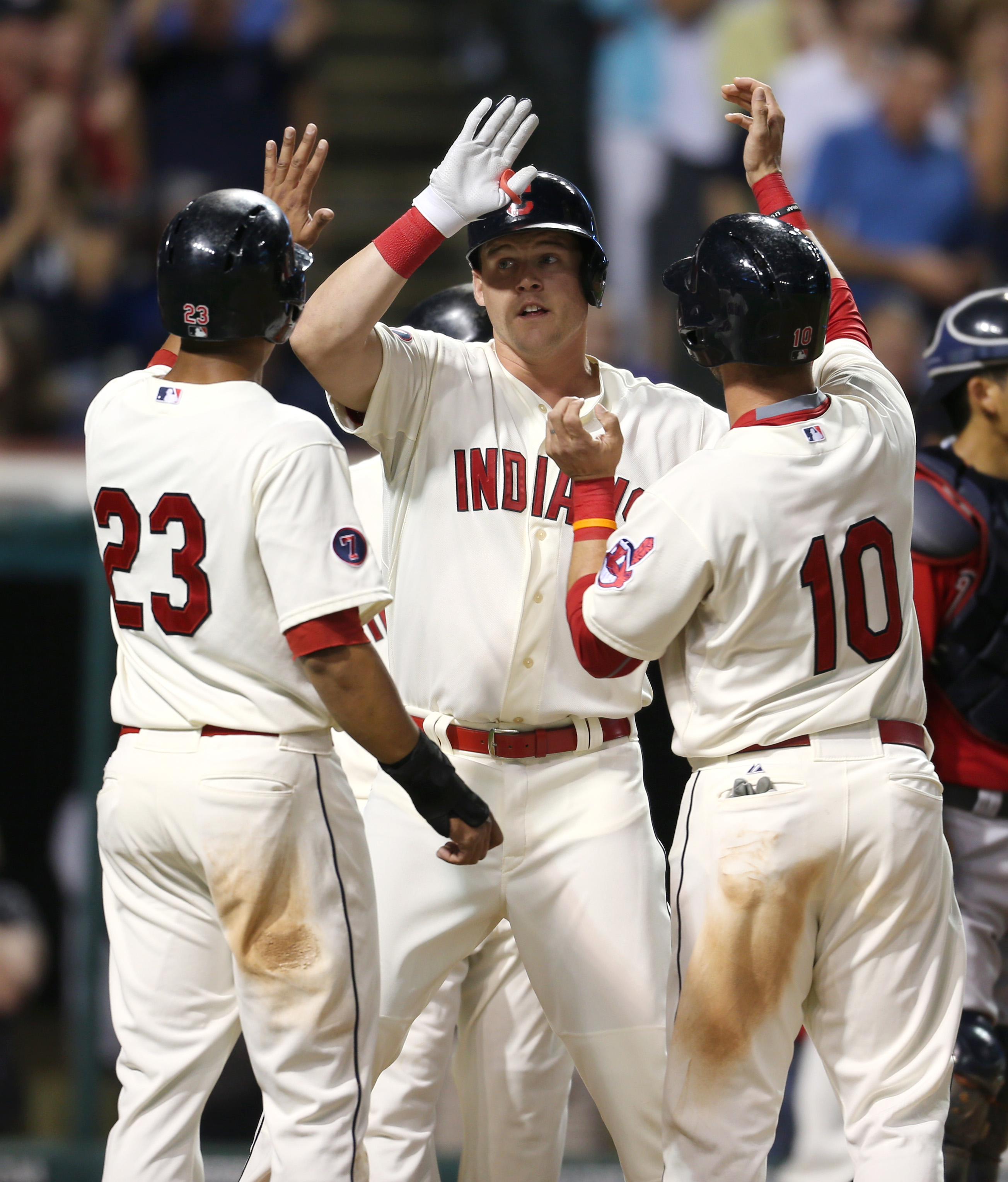 Cleveland Indians' Jerry Sands, center, is congratulated by teammates Michael Brantley, left, and Yan Gomes after hitting a grand slam off Minnesota Twins relief pitcher Blaine Boyer during the fifth inning of a baseball game, Saturday, Aug. 8, 2015, in C