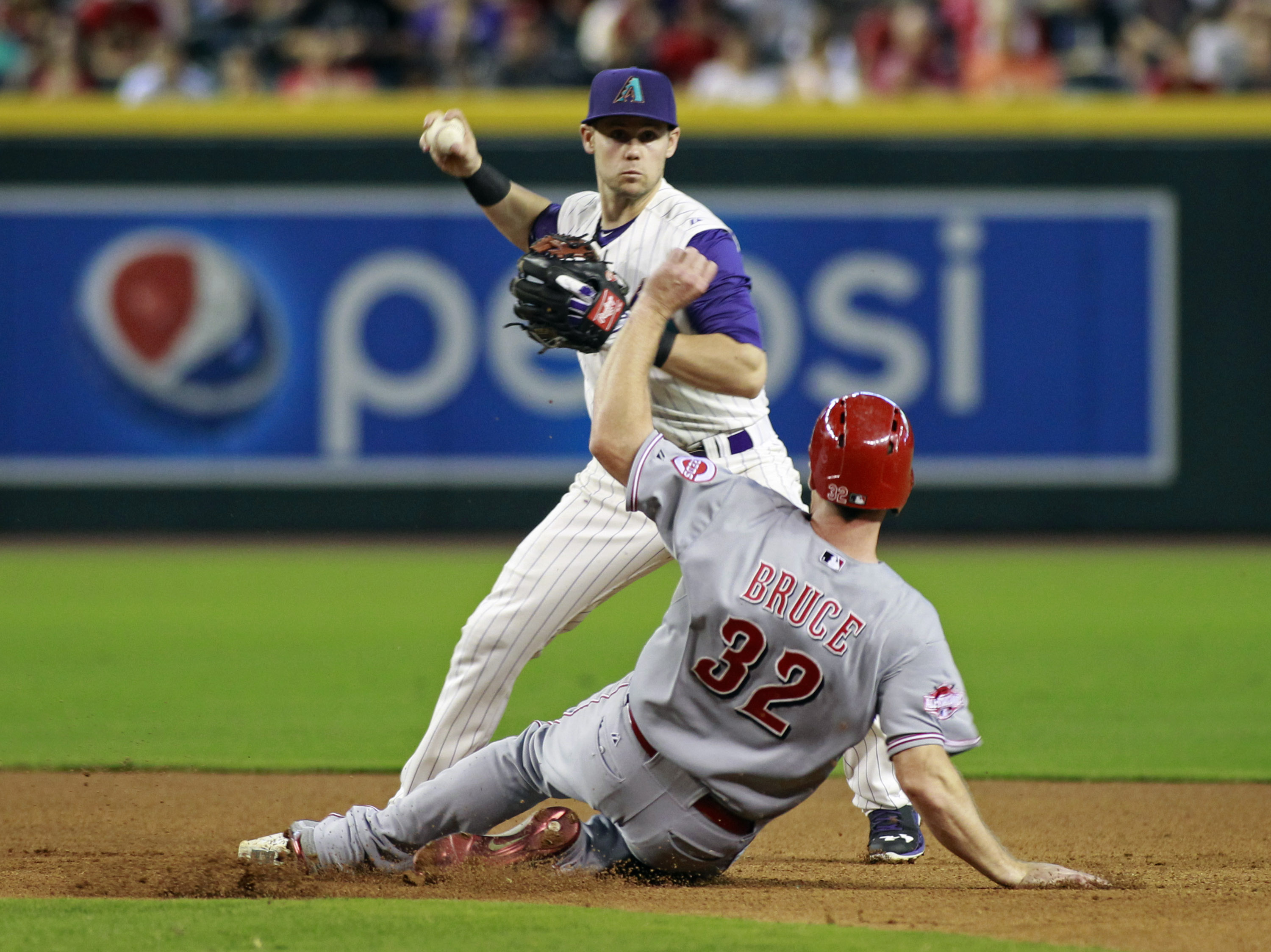 Arizona Diamondbacks' Chris Owings, top, looks to complete a double play as Cincinnati Reds' Jay Bruce slides into second during the fourth inning of a baseball game, Sunday, Aug. 9, 2015, in Phoenix. Owings was unable to complete the double play. (AP Pho