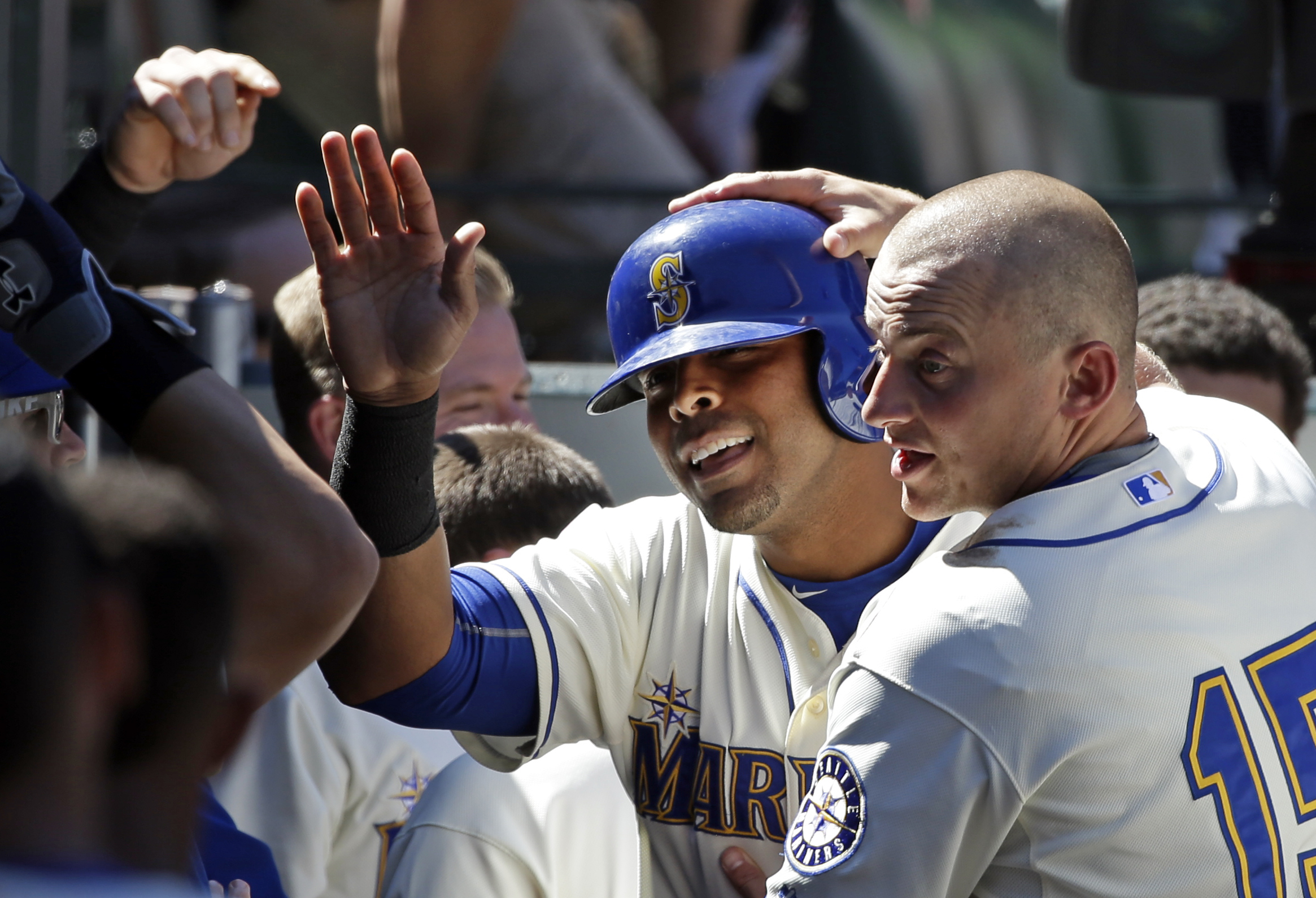 Seattle Mariners' Nelson Cruz, center, is congratulated after his home run by Kyle Seager (15) and teammates against the Texas Rangers in the sixth inning of a baseball game Sunday, Aug. 9, 2015, in Seattle. The Mariners won 4-2. (AP Photo/Elaine Thompson