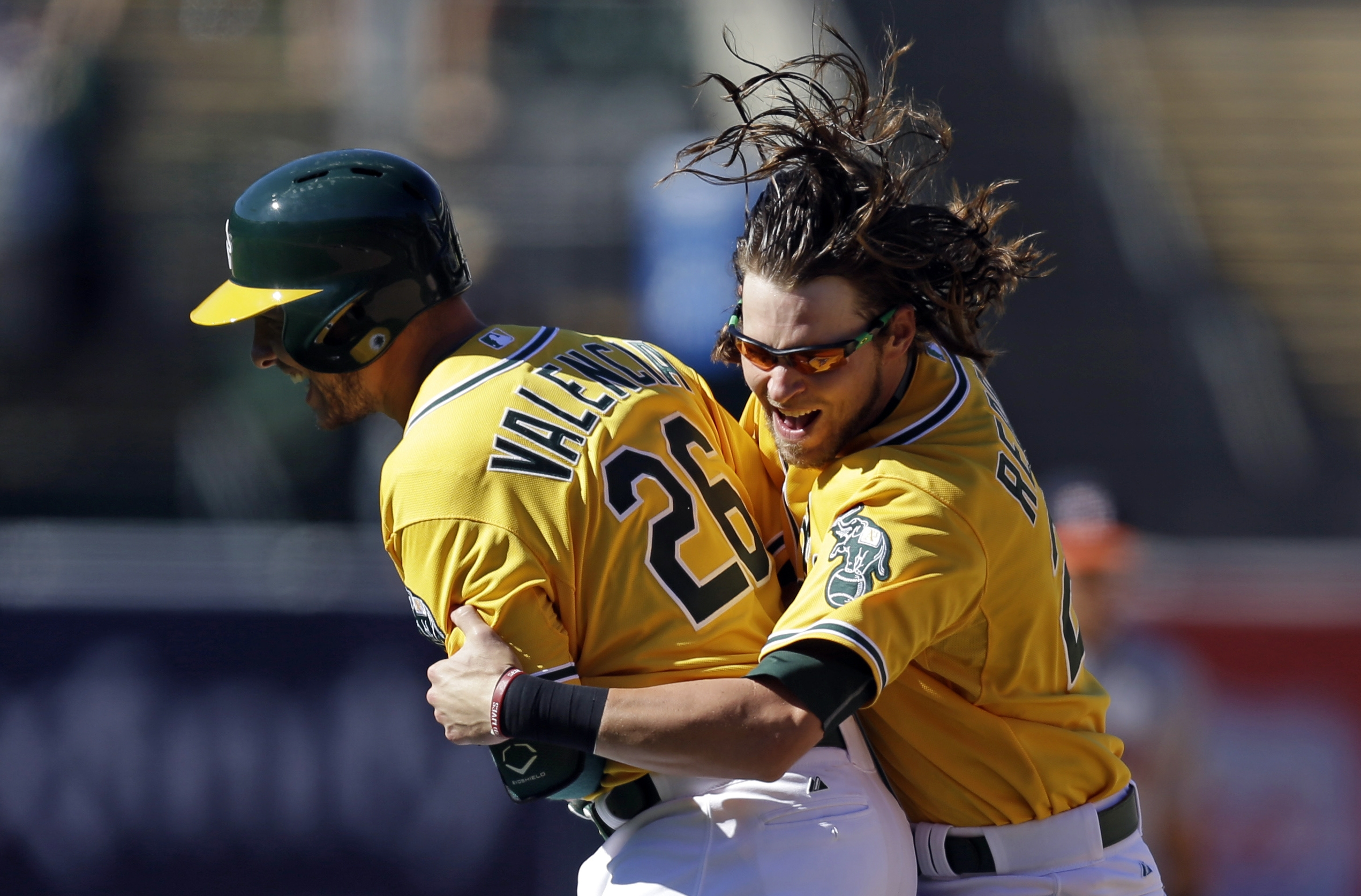 Oakland Athletics' Danny Valencia, left, is embraced by teammate Josh Reddick after making a baseball game-winning hit against the Houston Astros in the ninth inning Sunday, Aug. 9, 2015, in Oakland, Calif. The A's won 5-4. (AP Photo/Ben Margot)