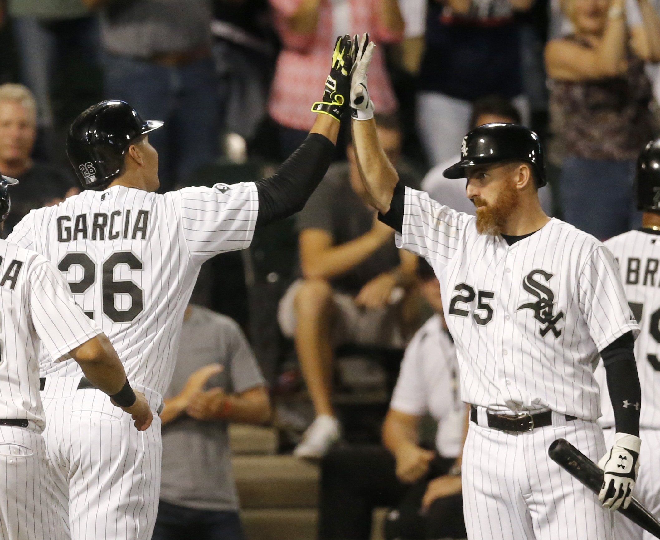 Chicago White Sox's Avisail Garcia, left, is greeted outside the dugout by Adam LaRoche (25) after Garcia hit a three-run home run off Los Angeles Angels starting pitcher Matt Shoemaker, also scoring Jose Abreu and Melky Cabrera, during the sixth inning o