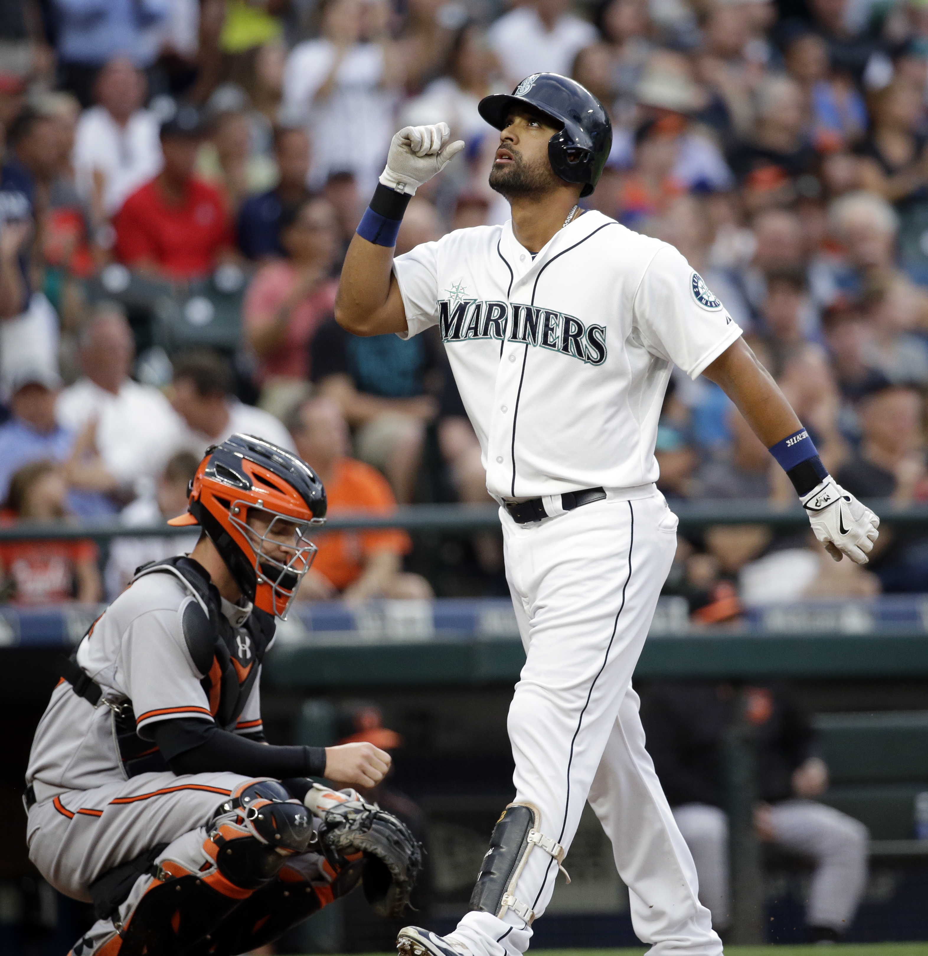 Seattle Mariners' Franklin Gutierrez, right, points skyward as he crosses home on his home run as Baltimore Orioles catcher Caleb Joseph looks away in the second inning of a baseball game Monday, Aug. 10, 2015, in Seattle. (AP Photo/Elaine Thompson)